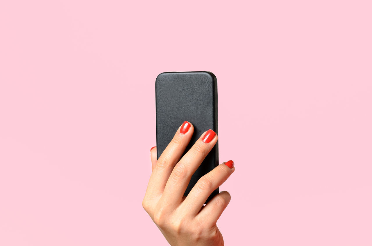 Adult close-up day human body part human hand Nail Polish one person people pink background pink color portable information device studio shot technology wireless technology