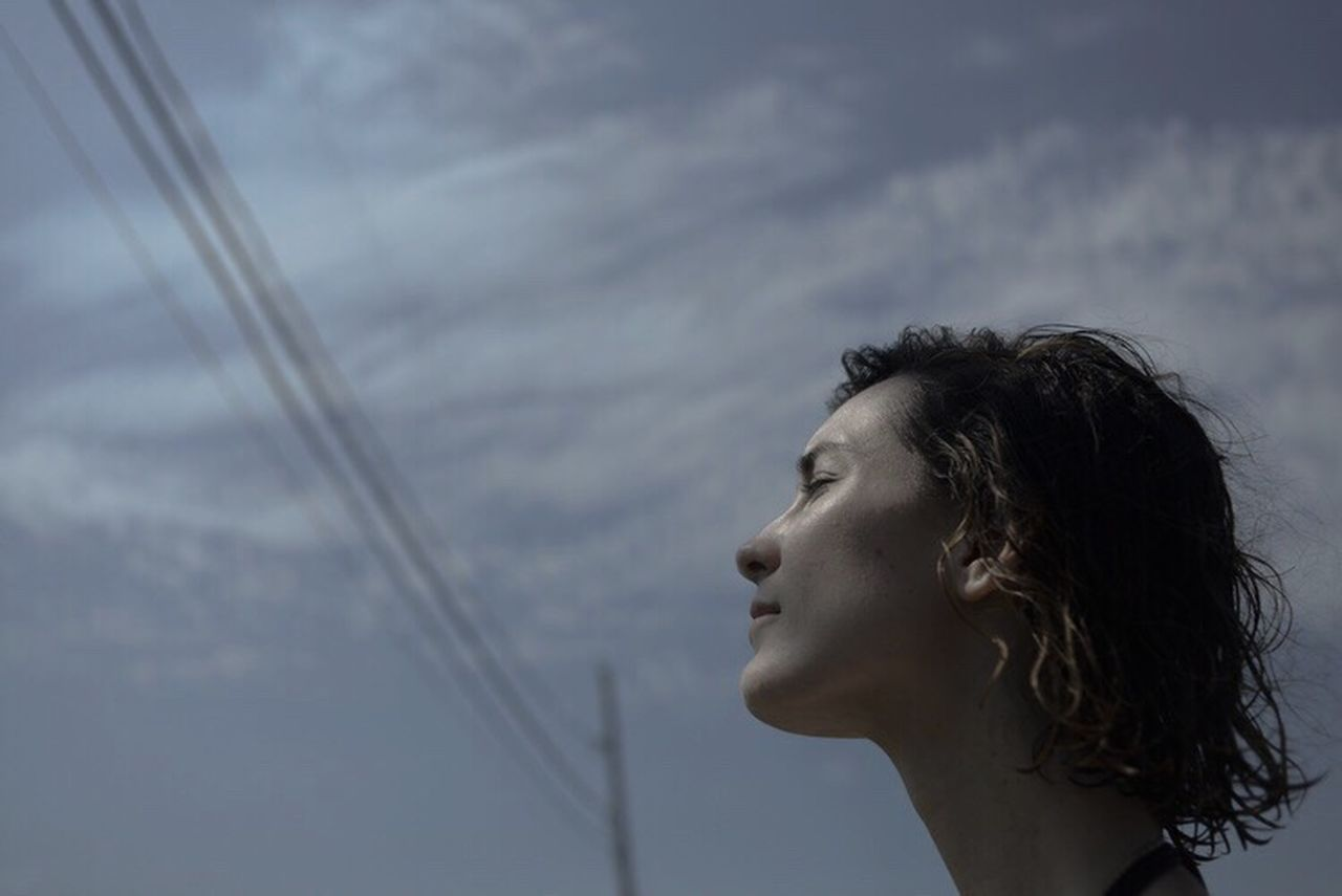 headshot, contemplation, sea, side view, cloud - sky, one person, young adult, only women, one woman only, profile view, beautiful woman, outdoors, day, one young woman only, sky, adults only, beauty, horizon over water, young women, adult, close-up, people