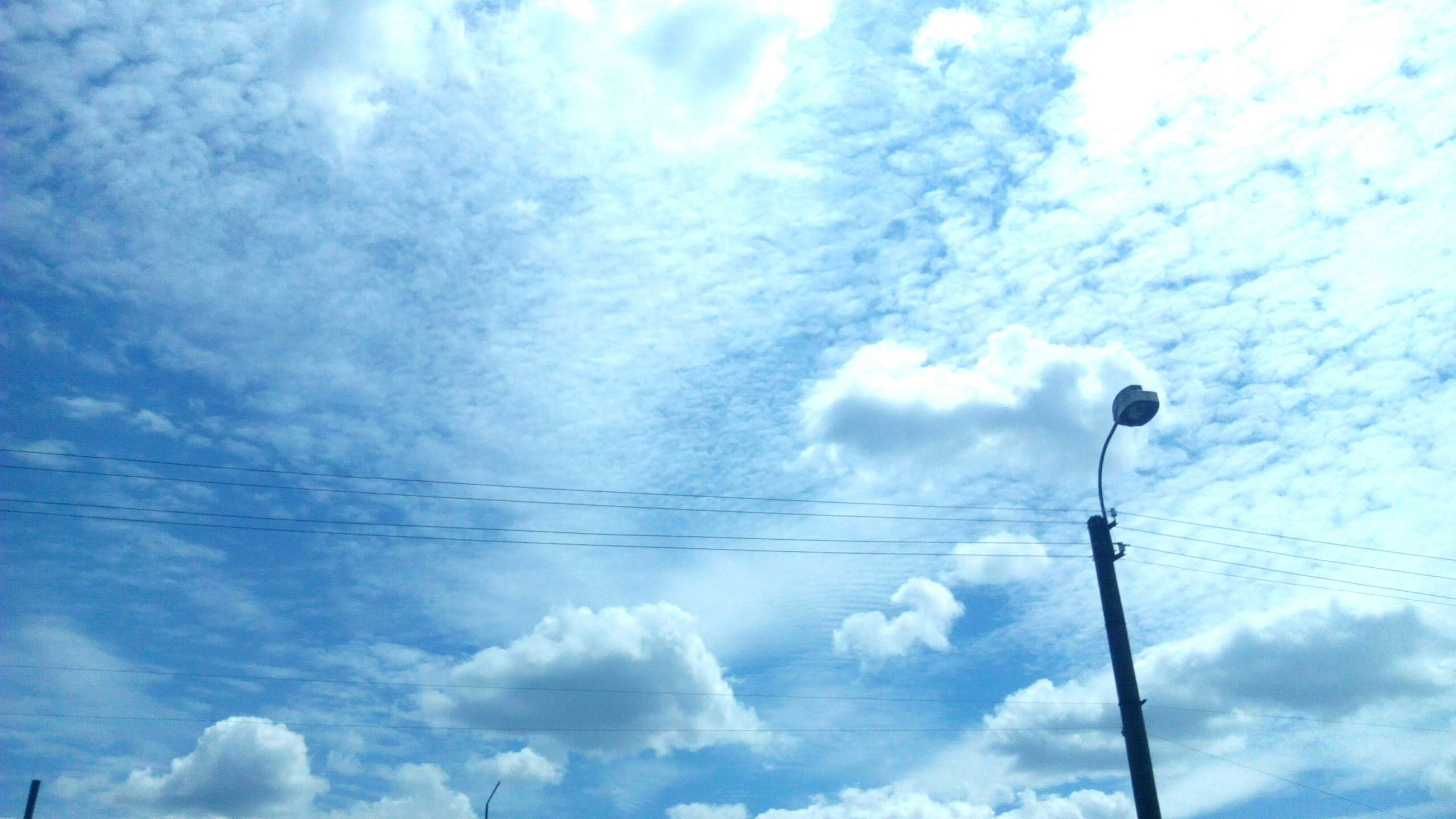 low angle view, sky, cloud - sky, power line, electricity, cloudy, street light, cable, lighting equipment, cloud, blue, power supply, connection, technology, electricity pylon, nature, pole, no people, outdoors, day