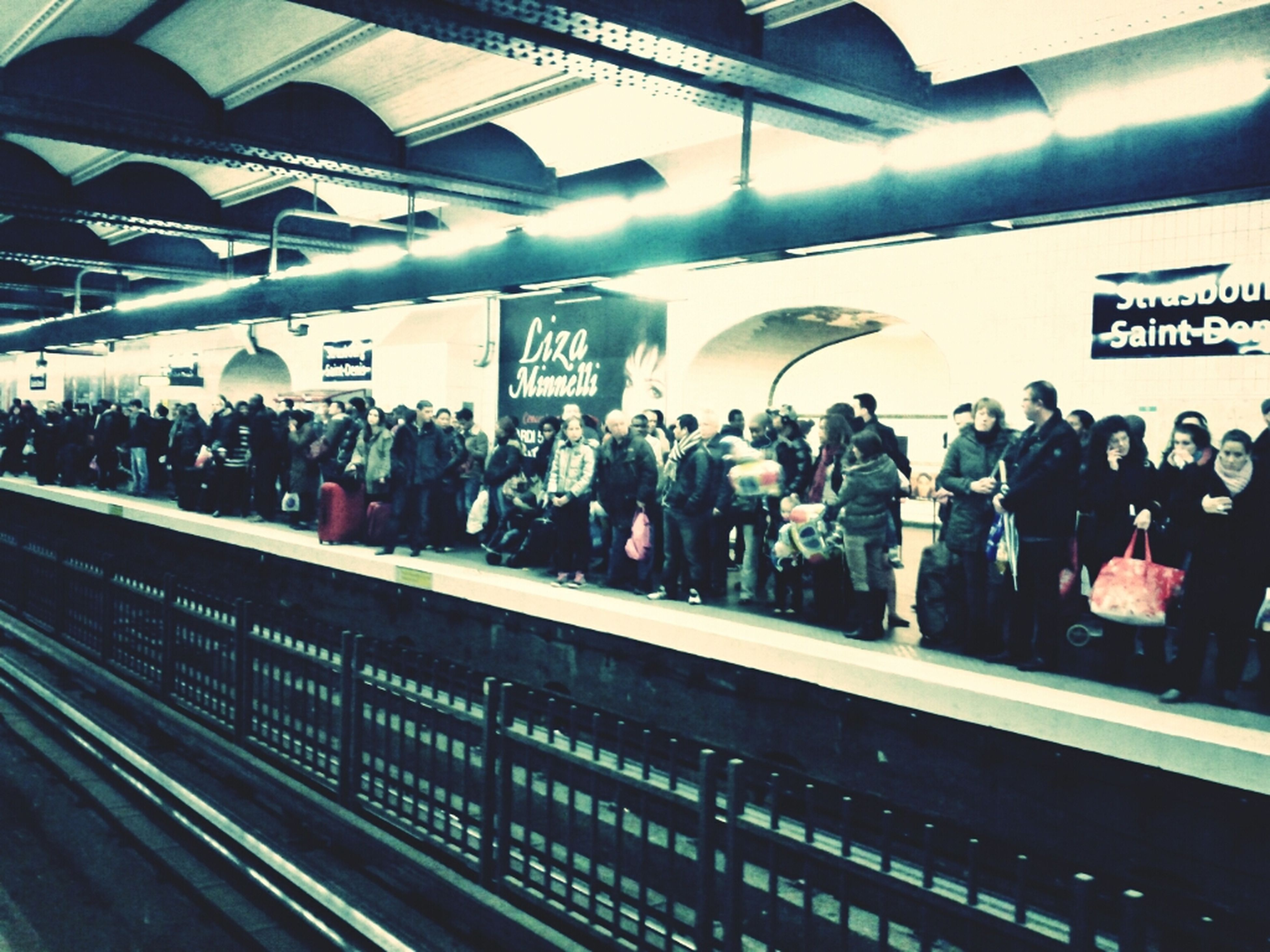 indoors, text, railroad station, large group of people, men, public transportation, person, lifestyles, illuminated, rail transportation, store, subway station, railroad station platform, transportation, retail, shopping mall, ceiling, western script, subway