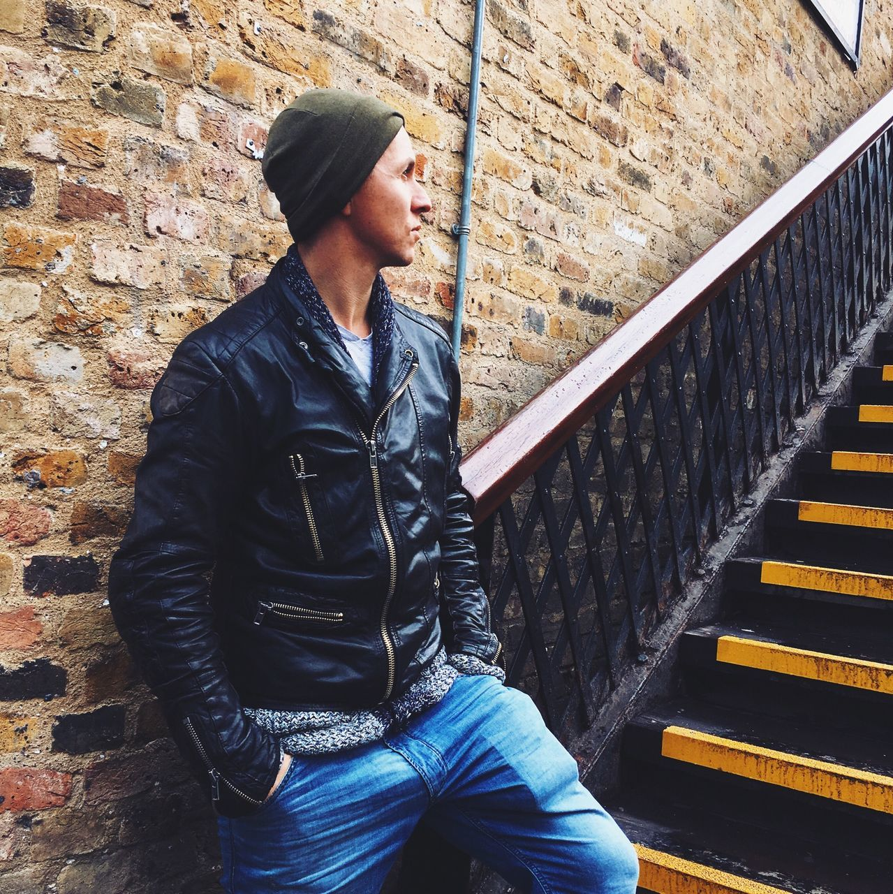 Young Man In Leather Jacket Standing By Stairs