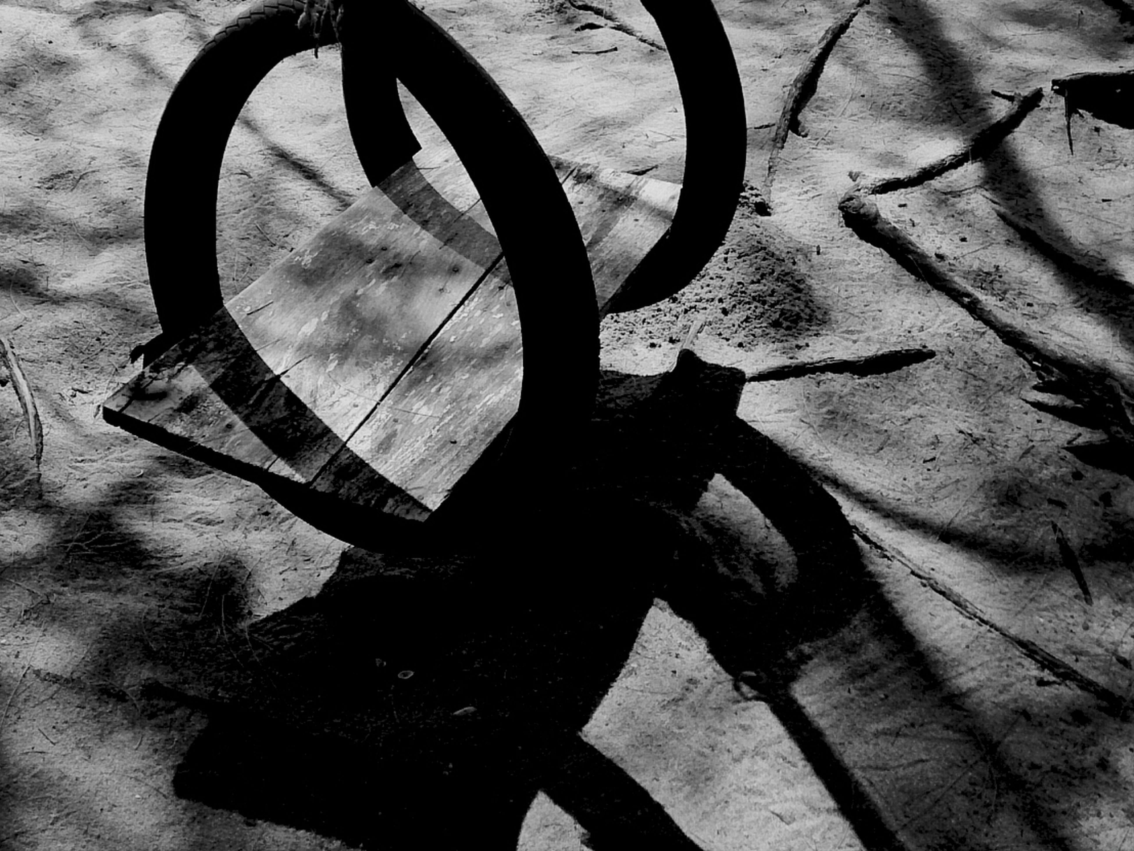 shadow, high angle view, sunlight, bicycle, wheel, close-up, street, outdoors, no people, day, metal, transportation, single object, ground, abandoned, wall - building feature, still life, part of, absence, metallic