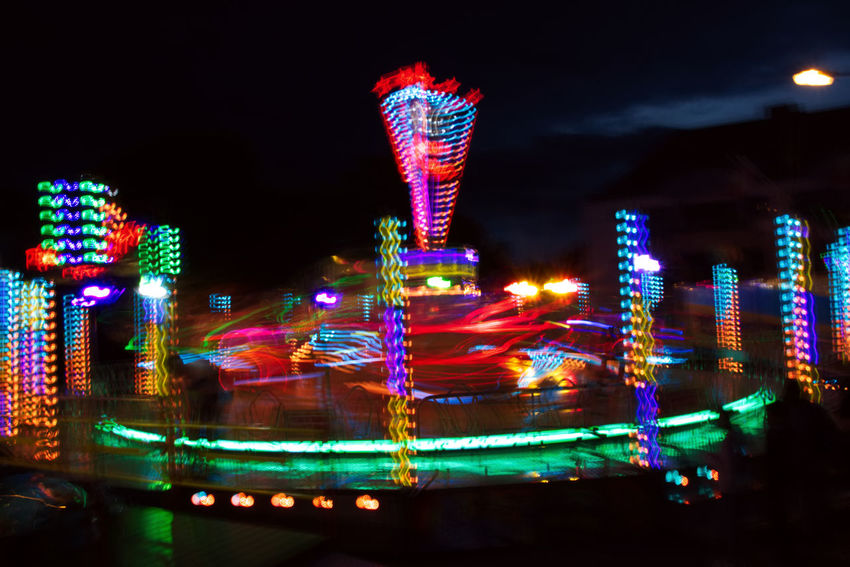Amusement Park Amusement Park Ride Architecture Arts Culture And Entertainment Blurred Motion Building Exterior Carousel Check This Out City Fair Ferris Wheel Illuminated Kermis Motion Multi Colored Neon Night No People Outdoors Sky Speed Street Streetphotography