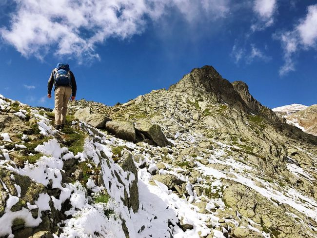 Hiking Mountain Backpack Sky Adventure Rock - Object Nature Cloud - Sky Exploration Day Real People Low Angle View Snow Full Length Outdoors Beauty In Nature One Person Scenics