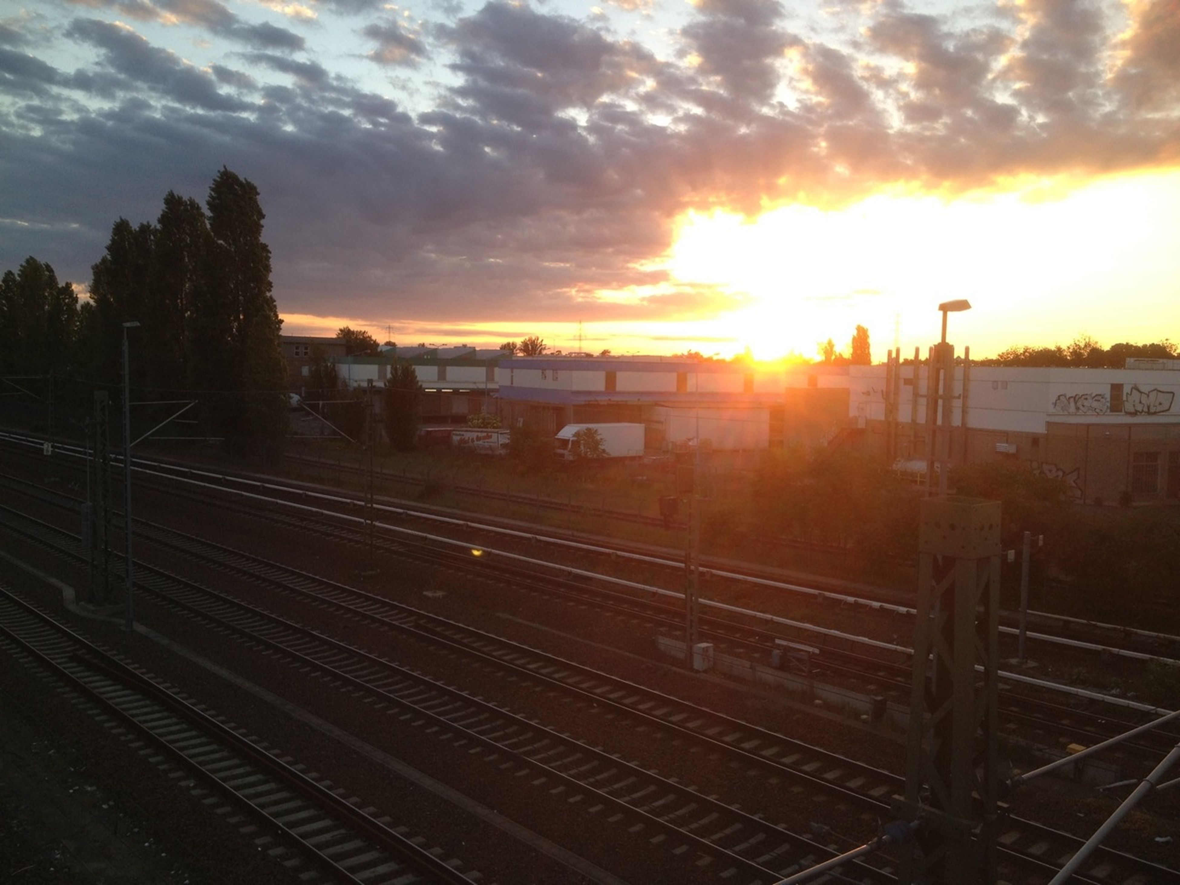 sunset, sky, cloud - sky, railroad track, sun, orange color, sunlight, silhouette, landscape, rail transportation, built structure, nature, sunbeam, cloud, scenics, beauty in nature, tranquil scene, tranquility, architecture, building exterior