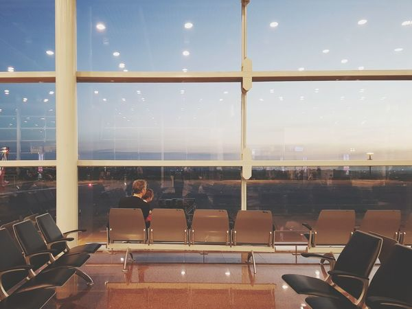 """""""No, I'll see the sun first"""" Sunrise Airport Airport Waiting Fatherhood Moments Moments Chair Window Business Finance And Industry Indoors  Seat No People City Modern Auditorium Architecture Airport Departure Area Day Cityscape"""
