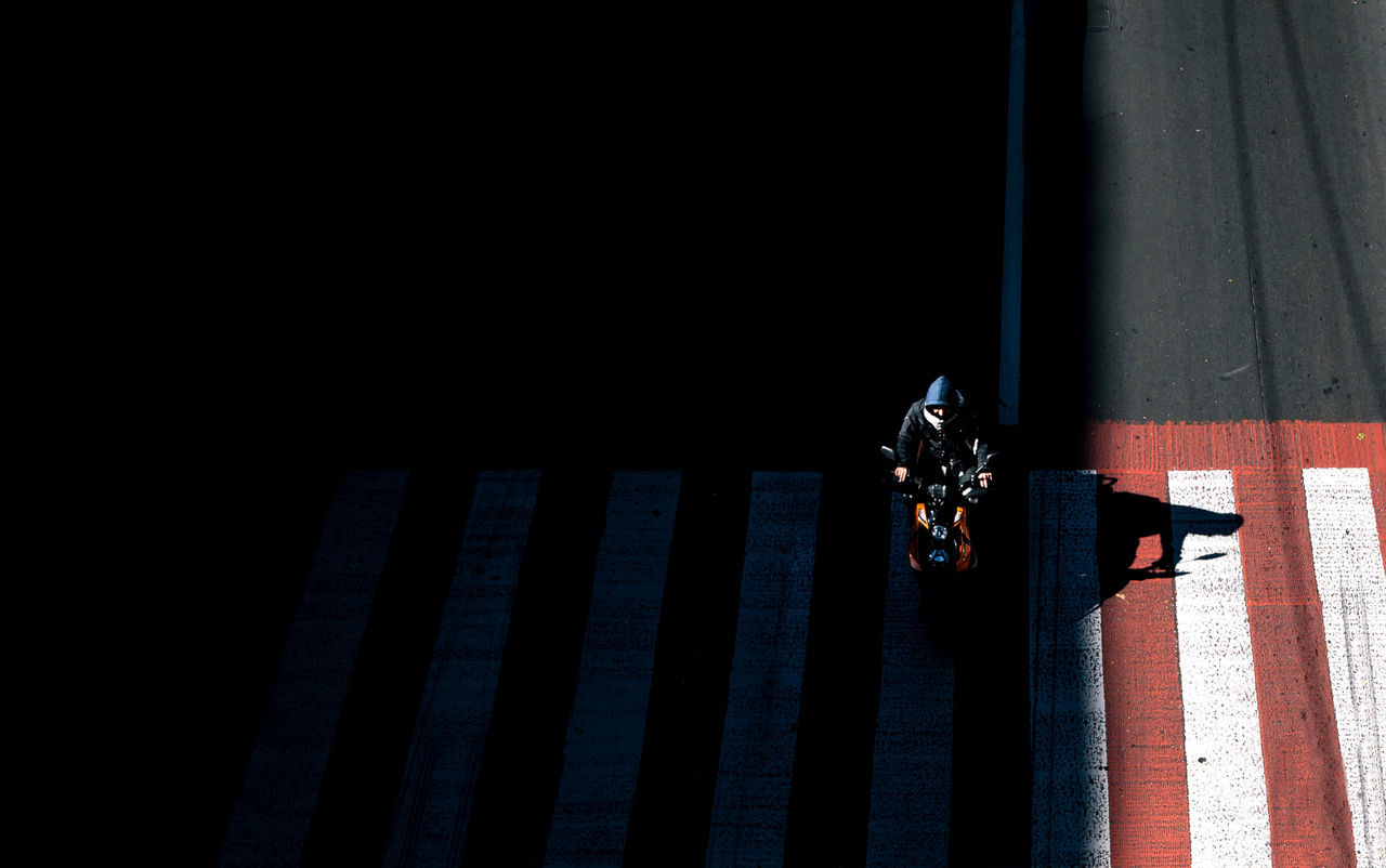 A lone biker with a closed face is lit by the sun. Light and shadow. Alone Biker Black Closed Crosswalk Day Light And Shadow One Person Outdoors Road Road Trip Shadow Striped Sunlight The Street Photographer - 2017 EyeEm Awards Let's Go. Together.