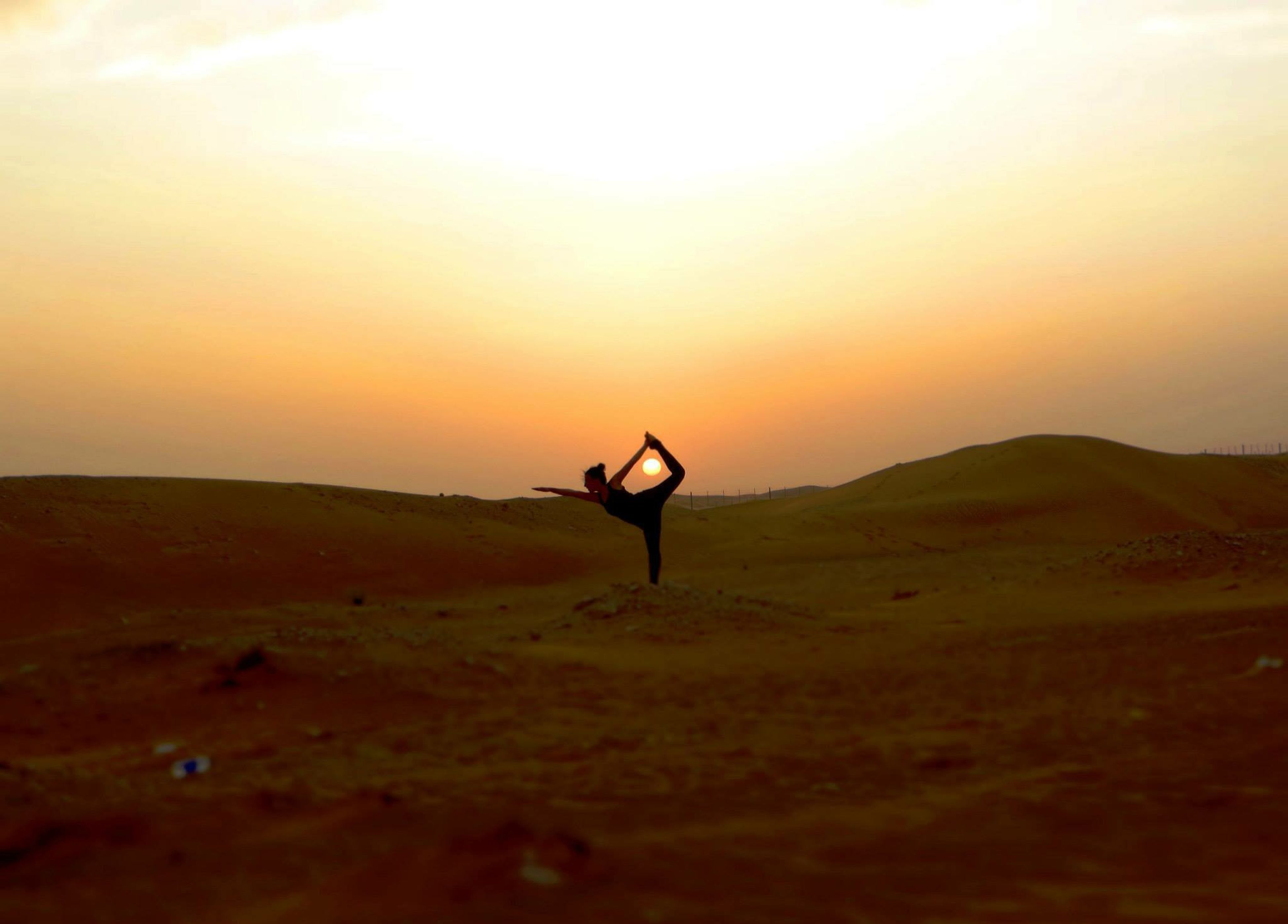 """Edge Of The World Alain Desert Yoga Yoga Pose Glitch so this yoga pose is called """"Bow and arrow"""". The sun perfectly placed in between the legs was an accident, but ended up fitting perfectly as it looks like the sun is right in the middle of the """"bow""""."""