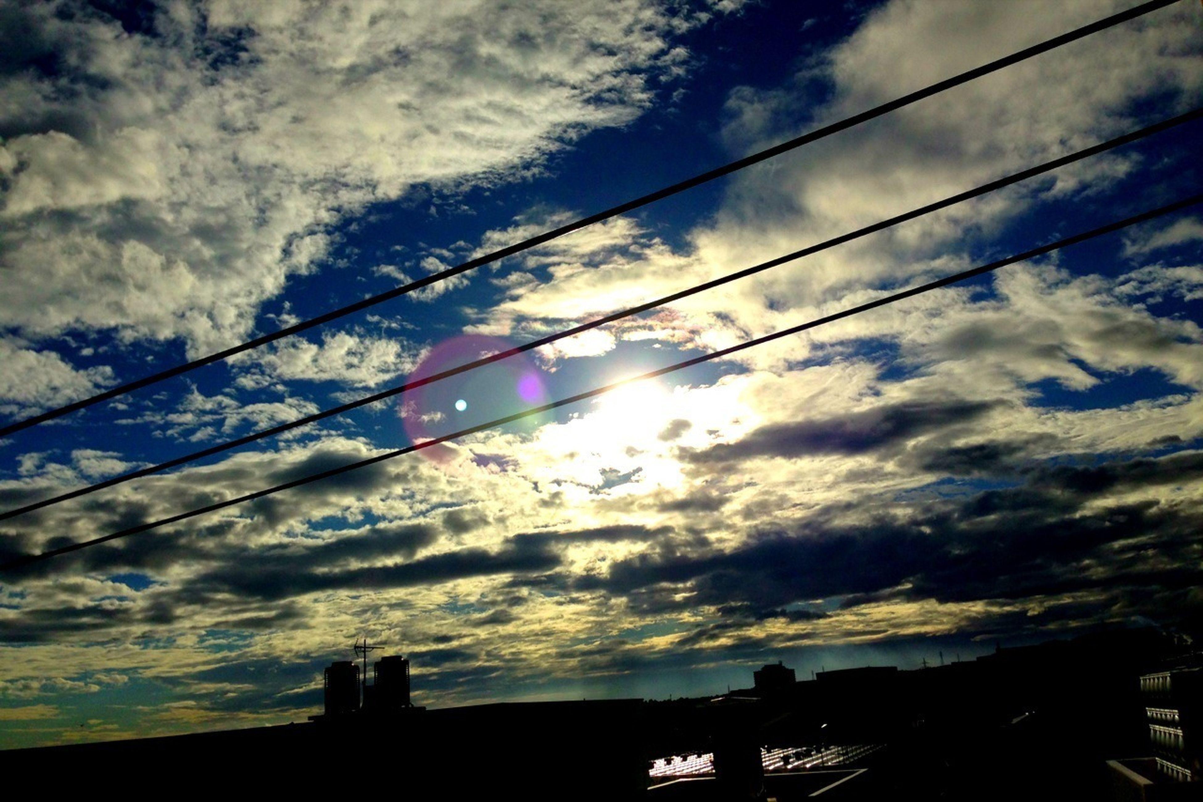 low angle view, sky, silhouette, cloud - sky, built structure, architecture, cloudy, cloud, building exterior, sunset, outdoors, nature, dusk, connection, cable, city, power line, building, no people, sunlight