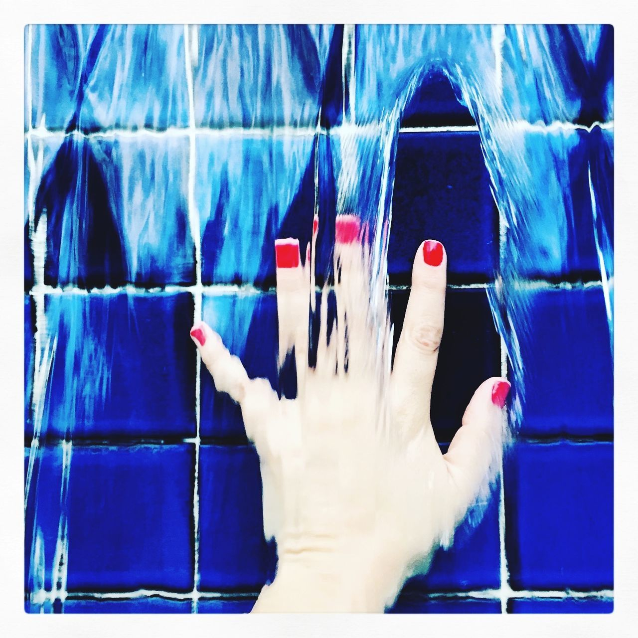 Water Falling On Cropped Hand Against Blue Wall