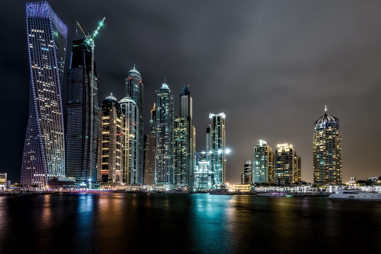 Cloudy night in Dubai Architecture Skyscraper Night Modern Urban Skyline Tower Illuminated Building Exterior City Built Structure Waterfront Cityscape Water No People Travel Destinations Sky Downtown District Reflection Long Exposure