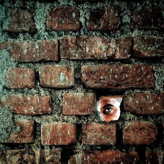 The first thing that came in my mind when I made this image was the song 'Another Brick In The Wall' by Pink Floyd. An Indian man looks on through a hole in a brick wall at a construction site in Ranchi, Jharkhand, India. Everydayeverywhere Dailylife Photojournalism Journalism Reportage Reportagespotlight Cityofcities Hufgpostgram Indiaphotoproject Onepluslife Oneplus2 Myfeatureshoot Ranchi Jharkhand India ASIA