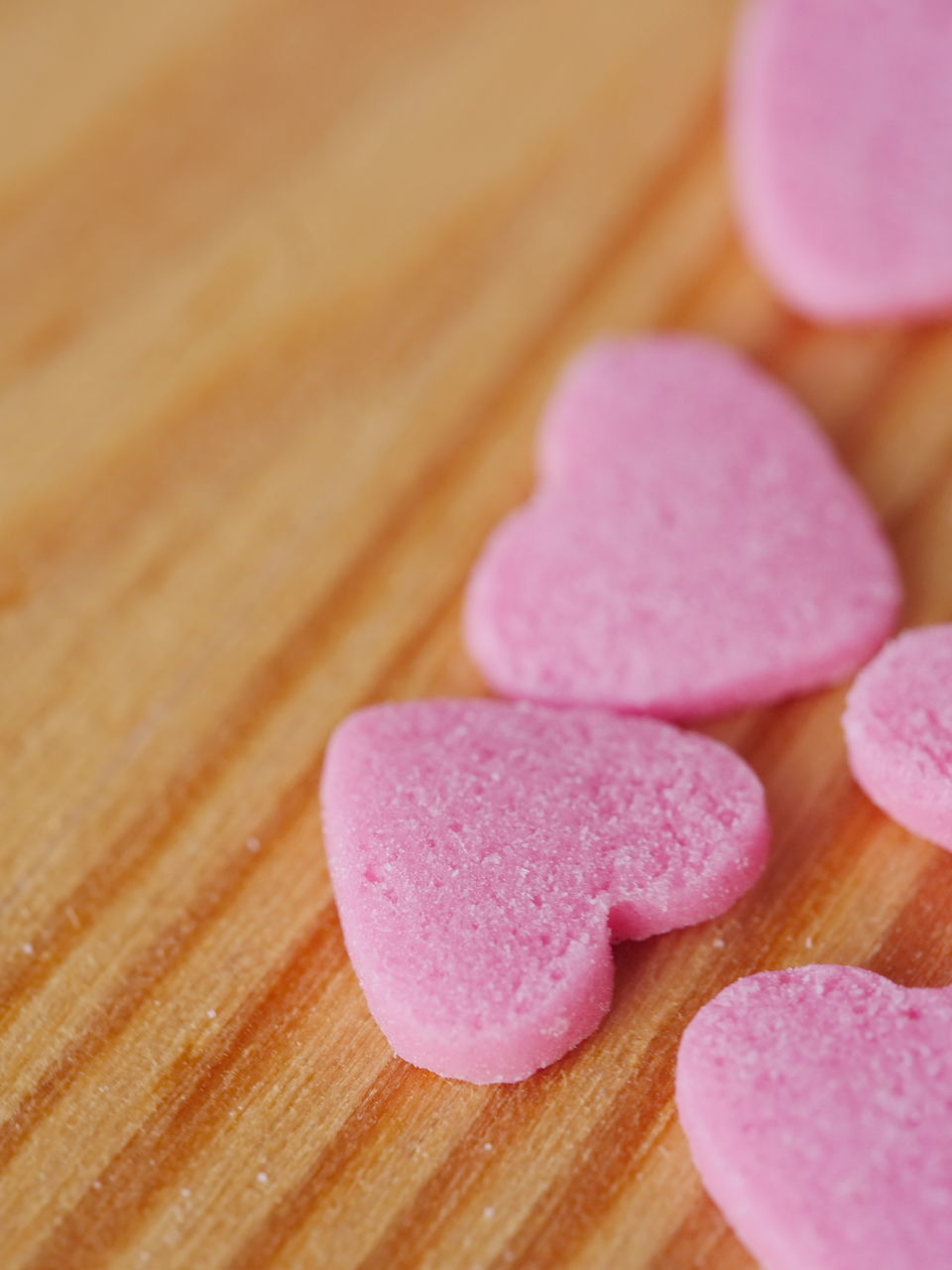 High Angle View Of Heart Shape Candies On Wooden Table