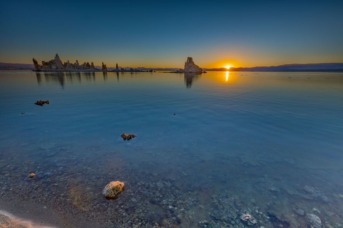 Sunrise at Mono Lake | The sun rose at Mono Lake. It was so calm and surreal. One of the largest desert lakes you can visit, and here I was appreciating the drastic temperature change as soon as the sun rose over the mountains. Mono Lake, California Beauty In Nature Blue California Calm Clarity Clear Water Desert Desert Lake Lake Landscape Landscape Photography Mono Lake Nature Non-urban Scene Outdoors Reflection Remote Rock Formations Rocks Sky South Tufa Sun Sunrise Tranquility Water