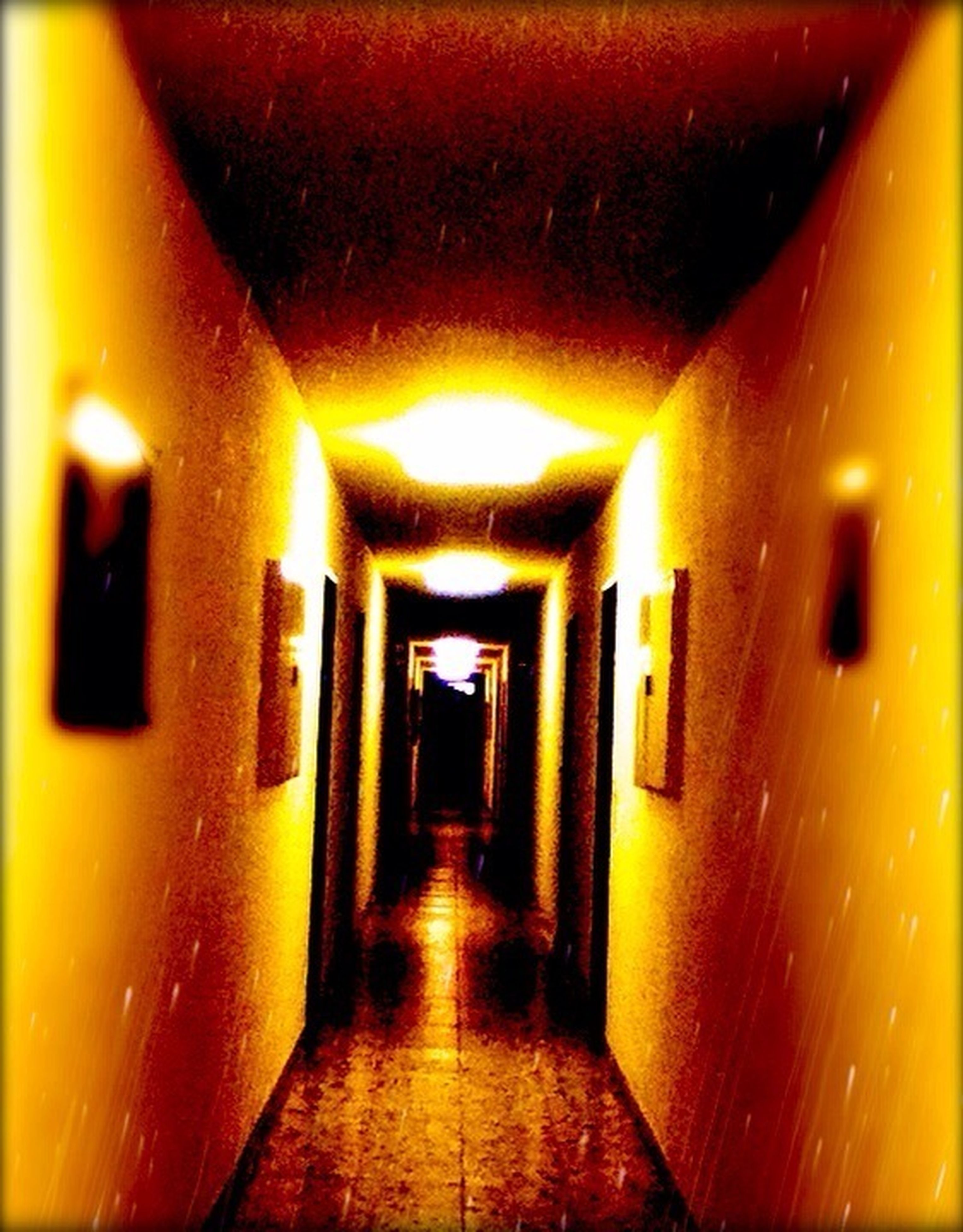 illuminated, architecture, the way forward, lighting equipment, built structure, indoors, diminishing perspective, night, empty, wall - building feature, orange color, corridor, light - natural phenomenon, vanishing point, glowing, yellow, electric light, lit, in a row, no people
