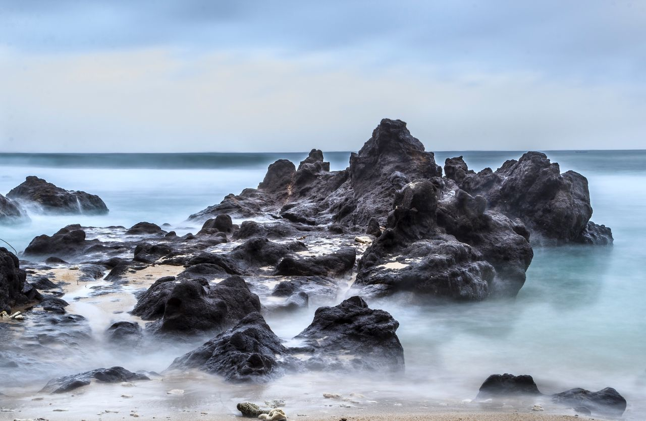 Rock Formations In Sea Against Cloudy Sky