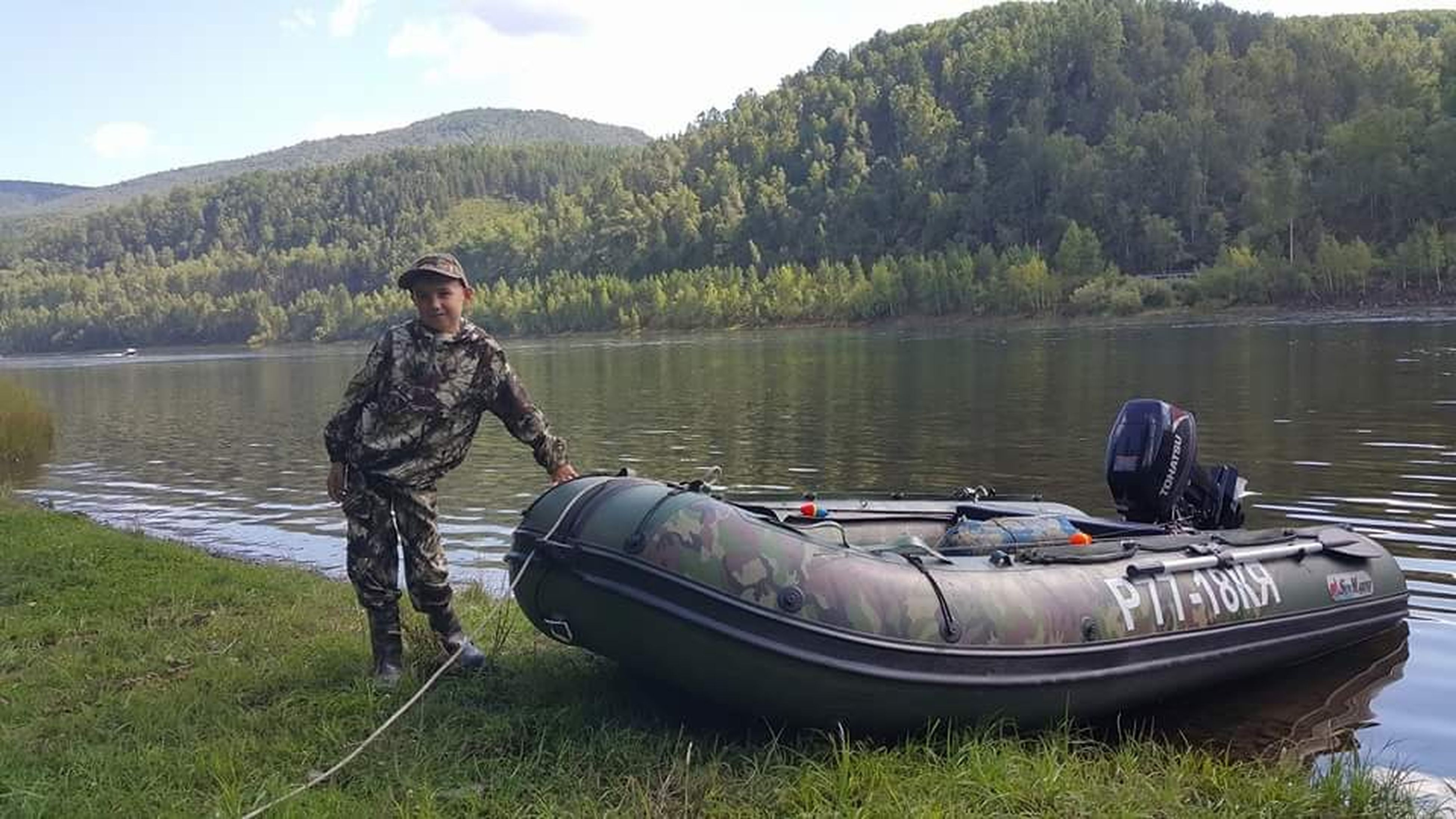 lake, real people, water, day, nature, standing, leisure activity, outdoors, nautical vessel, tree, transportation, lifestyles, one person, men, full length, looking at camera, sky, military uniform, beauty in nature, young adult, camouflage clothing, people