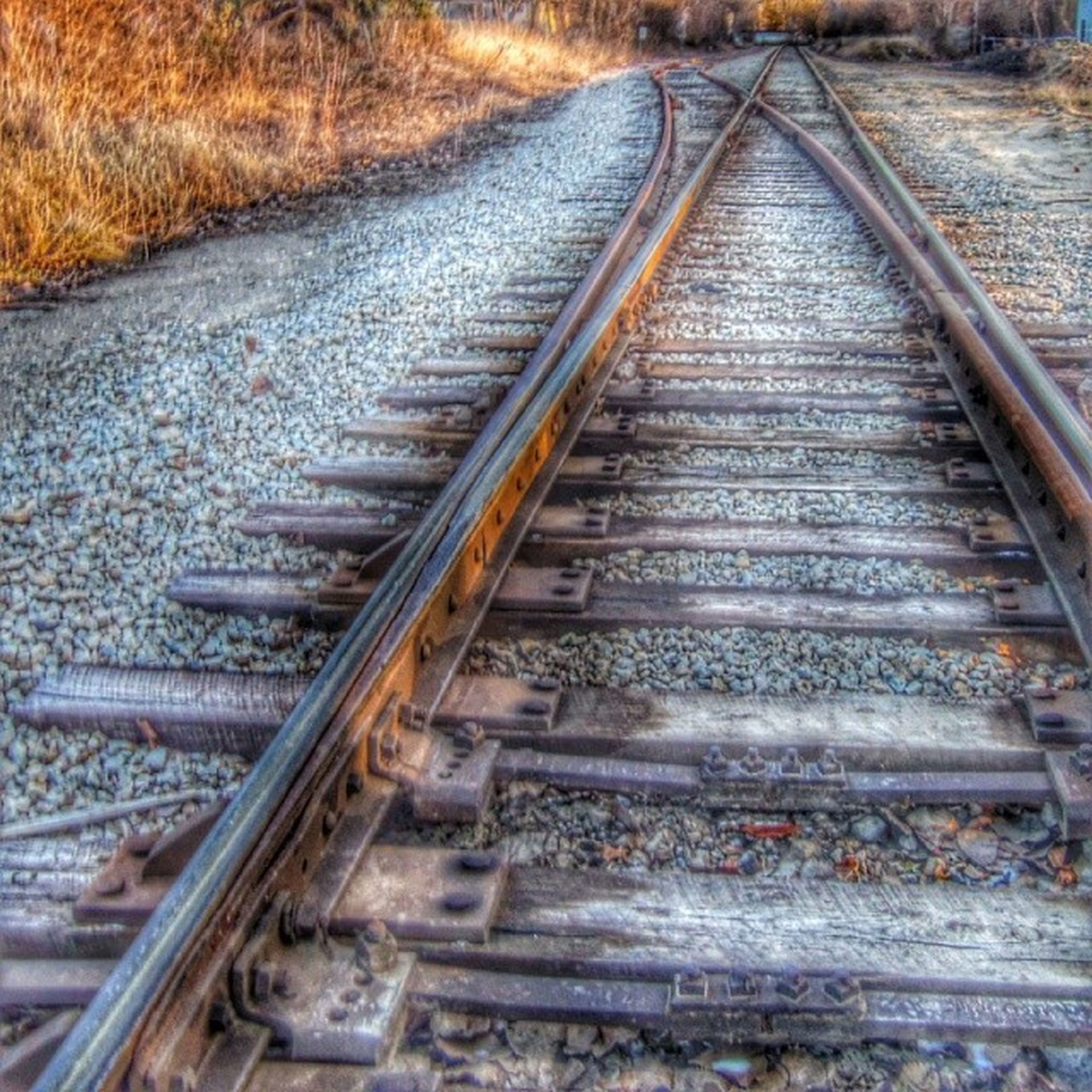 railroad track, transportation, the way forward, diminishing perspective, rail transportation, vanishing point, railway track, straight, metal, day, high angle view, long, no people, connection, outdoors, public transportation, surface level, gravel, rusty, metallic