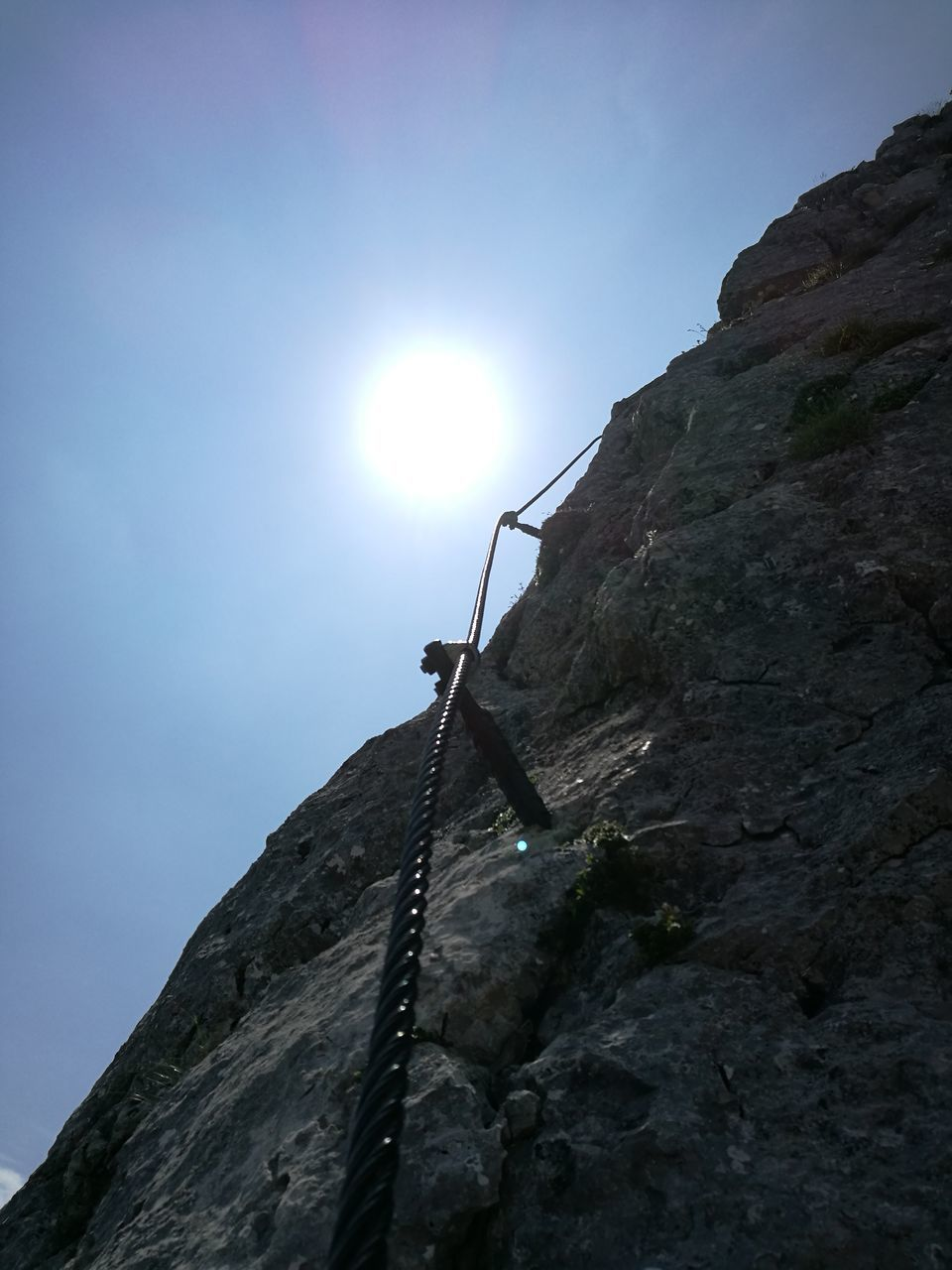 climbing, low angle view, rock climbing, rock - object, rope, lens flare, sun, sunlight, mountain, adventure, cliff, outdoors, strength, day, extreme sports, nature, challenge, sky, rock face, clear sky, no people