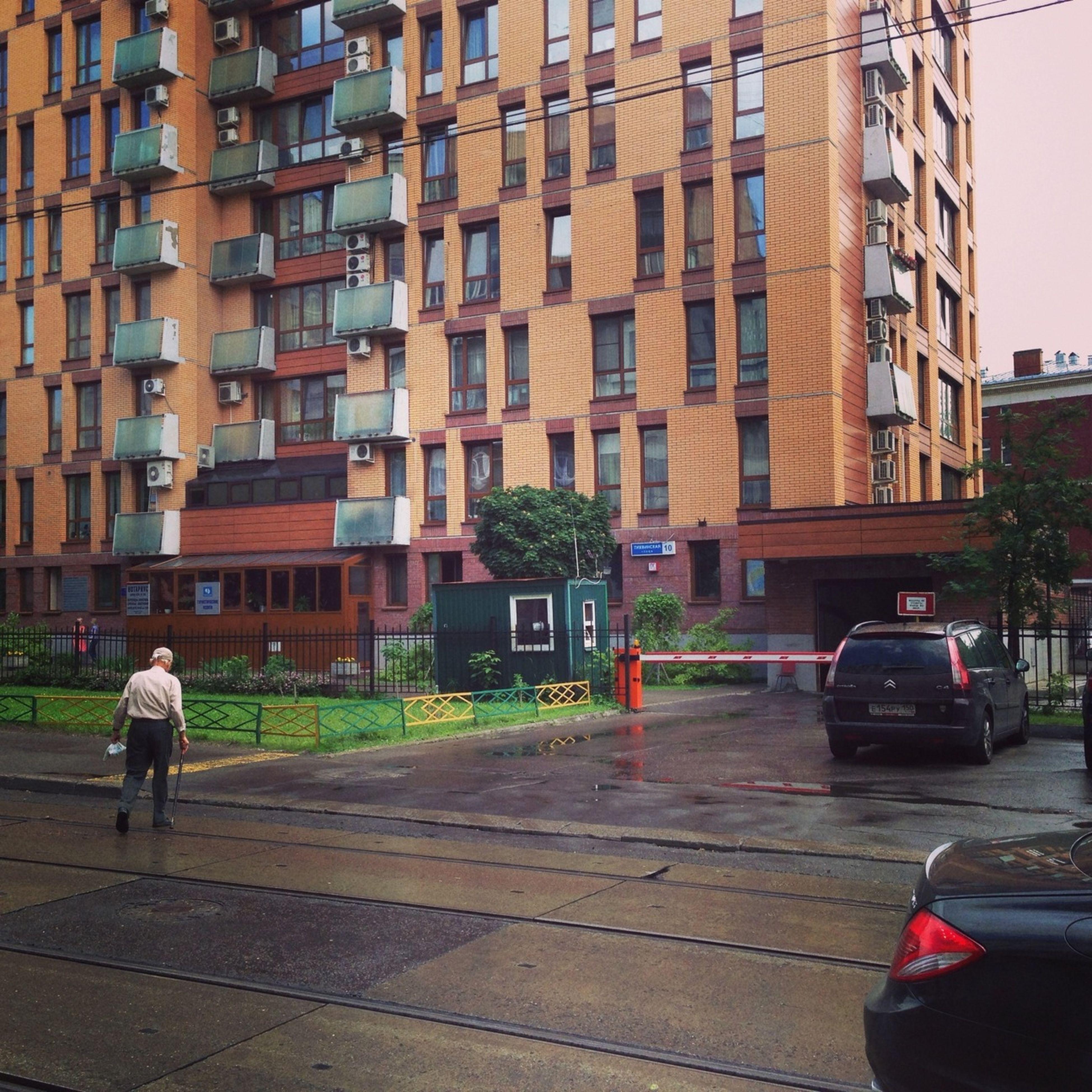building exterior, architecture, built structure, city, street, transportation, car, land vehicle, city life, walking, mode of transport, road, men, city street, incidental people, building, person, sidewalk