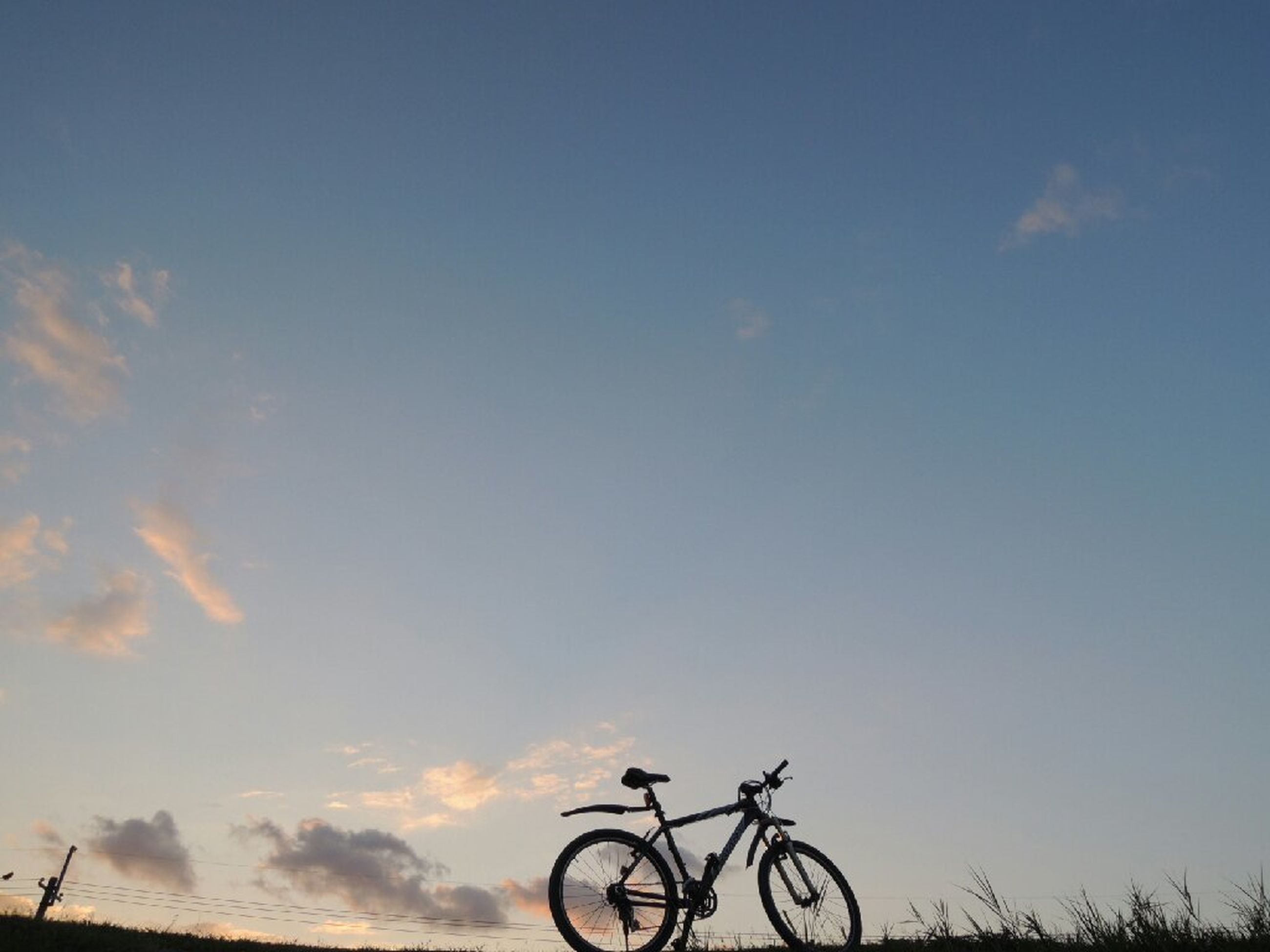 bicycle, transportation, mode of transport, land vehicle, stationary, parked, parking, sky, copy space, silhouette, clear sky, no people, outdoors, cycling, tranquility, low angle view, nature, day, sunlight, riding