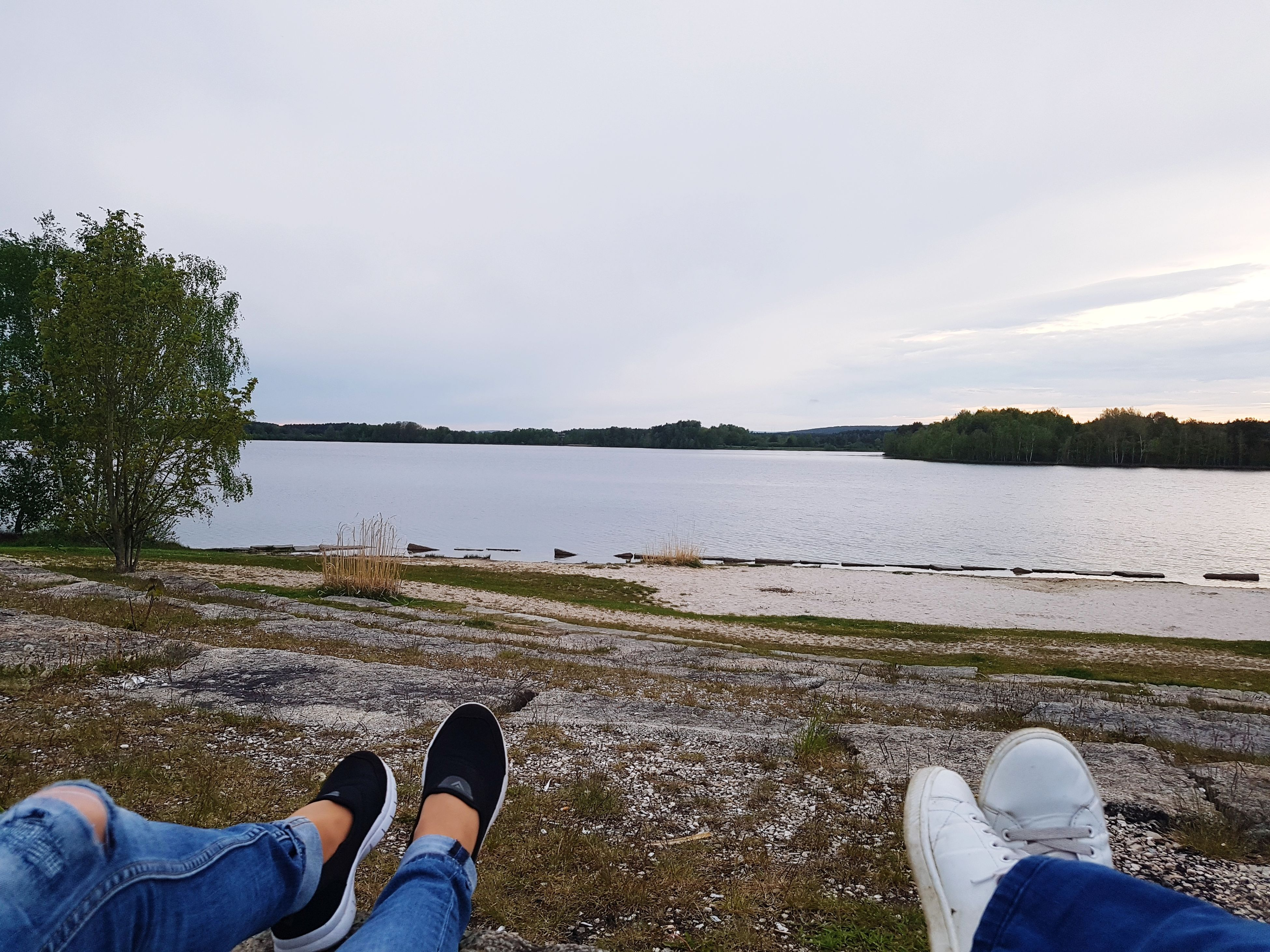 shoe, low section, human leg, water, personal perspective, real people, nature, outdoors, day, human body part, leisure activity, beauty in nature, river, sky, tranquility, cloud - sky, riverbank, men, scenics, lifestyles, standing, tree, grass, people