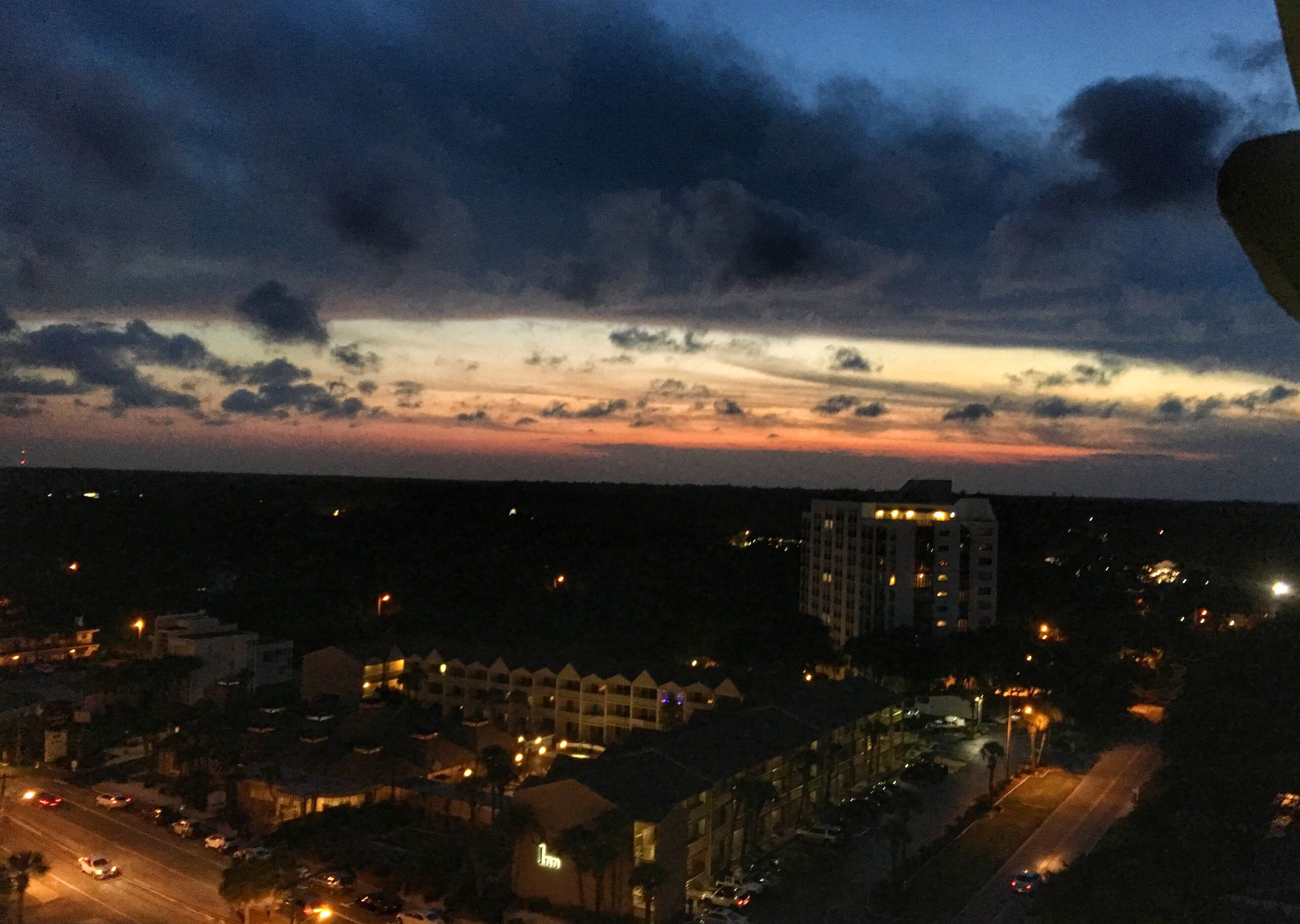 illuminated, city, sky, cityscape, architecture, built structure, cloud - sky, night, sunset, city life, residential building, residential district, cloudy, dramatic sky, aerial view, cloud, outdoors, weather, no people, landscape, dark, elevated view, nature, overcast