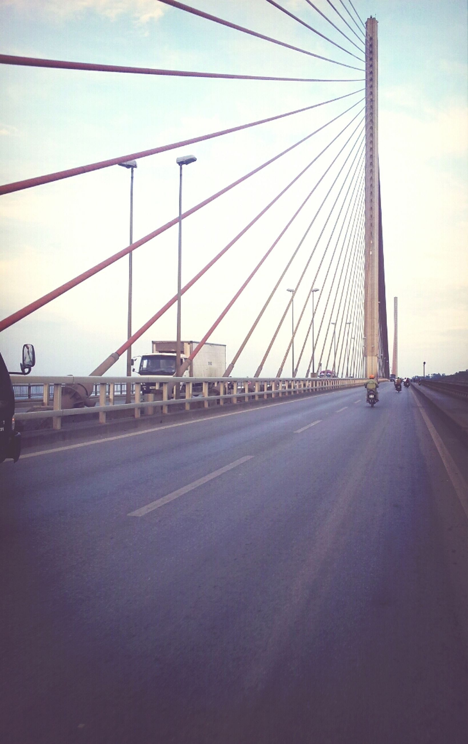 transportation, the way forward, road, road marking, sky, diminishing perspective, connection, built structure, architecture, vanishing point, car, bridge - man made structure, street, land vehicle, cloud - sky, long, mode of transport, engineering, empty, cloud