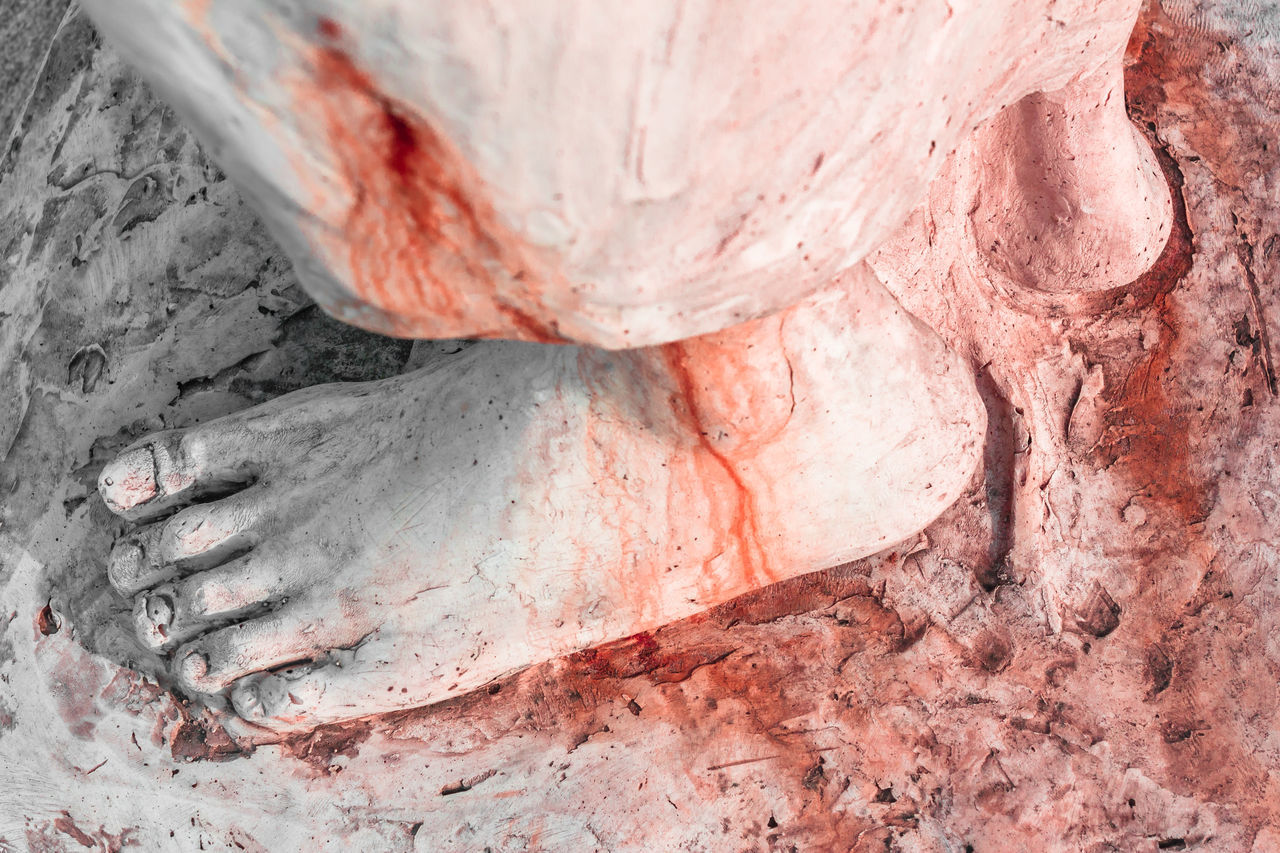 Extreme close-up of the feet of Jesus Christ bloodied. Top view. Shallow depth of field. Art Bible Blood Bloodied Calvary Catholic Christ Christian Christianity Death Detail Easter Faith Feet Foot God Holy Icon Isolated Jesus Love Nail Pain Passion Pray