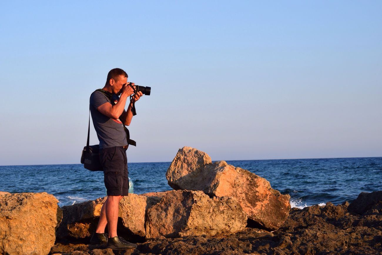 Sea Photography Themes Photographing Camera - Photographic Equipment Horizon Over Water Rock - Object Water Standing Full Length One Person Photographer Real People Leisure Activity Outdoors Technology Day Nature Sky Beauty In Nature Men