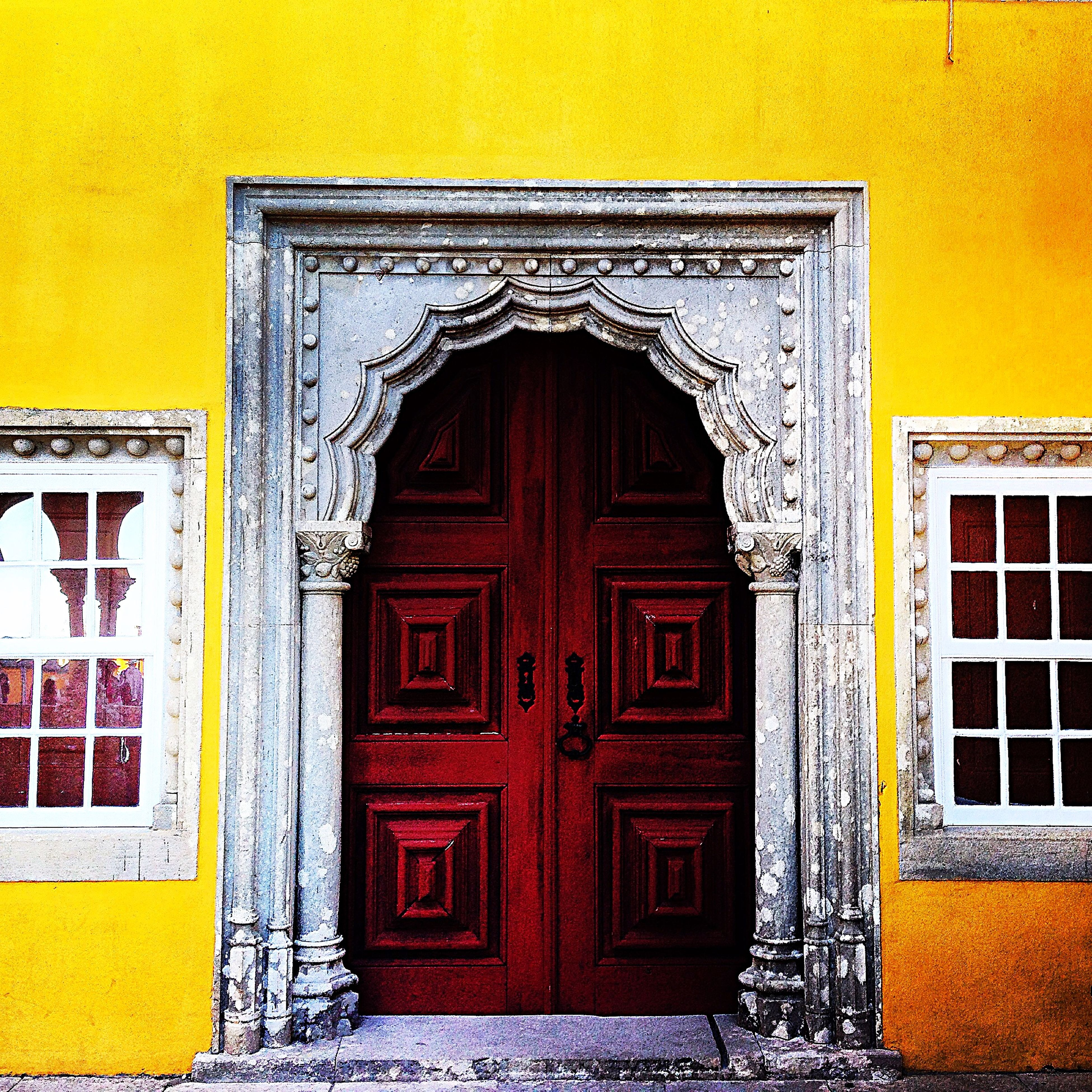 architecture, building exterior, built structure, yellow, door, closed, entrance, window, house, facade, outdoors, wall - building feature, orange color, arch, day, residential structure, no people, wall, building, old