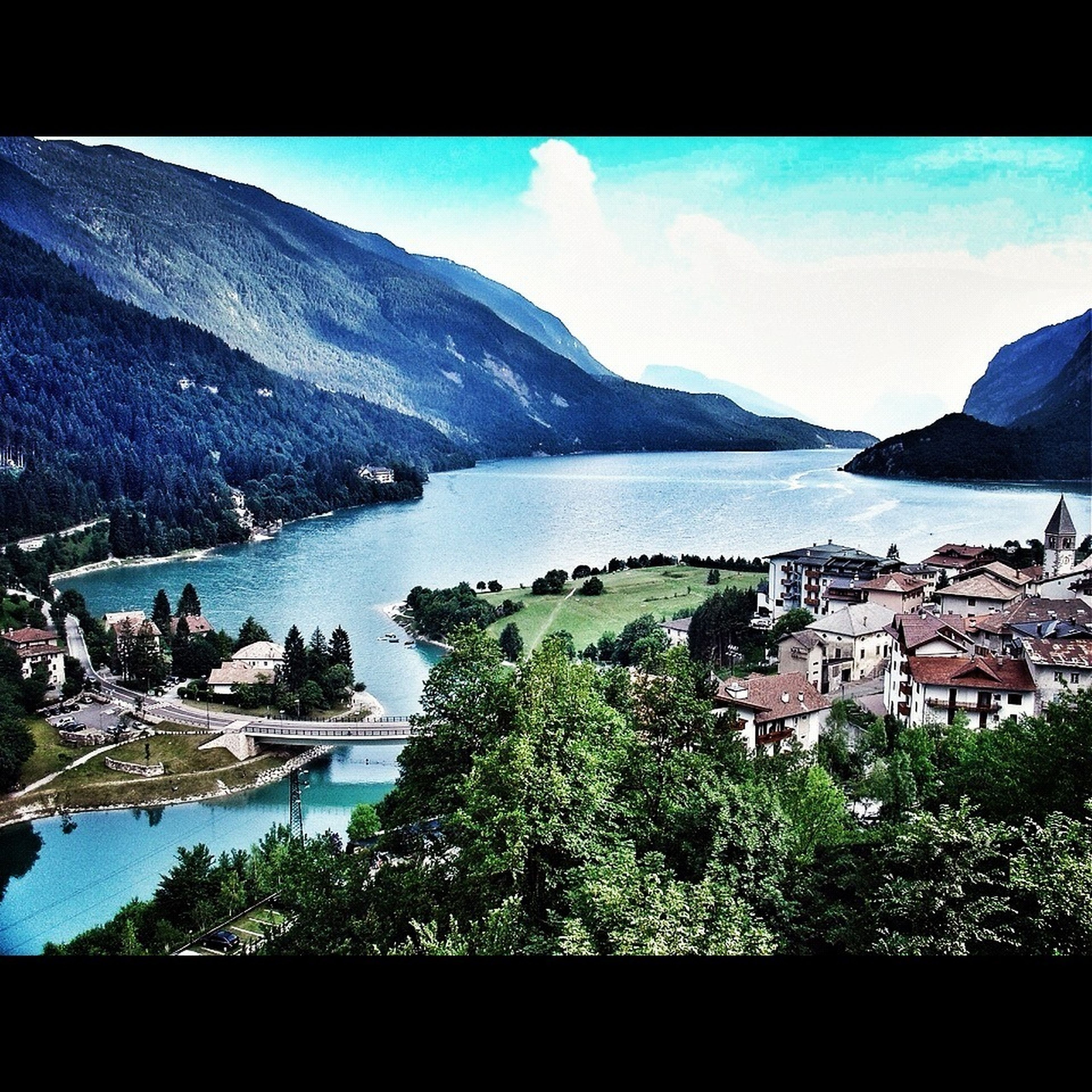 water, mountain, building exterior, architecture, built structure, sky, sea, house, transfer print, town, mountain range, residential structure, scenics, tree, lake, blue, nature, high angle view, townscape, beauty in nature