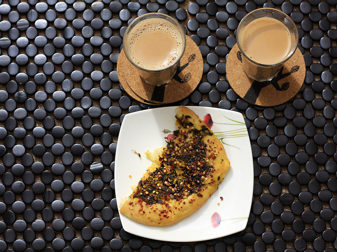 High Angle View Of Tea And Pizza On Patterned Table