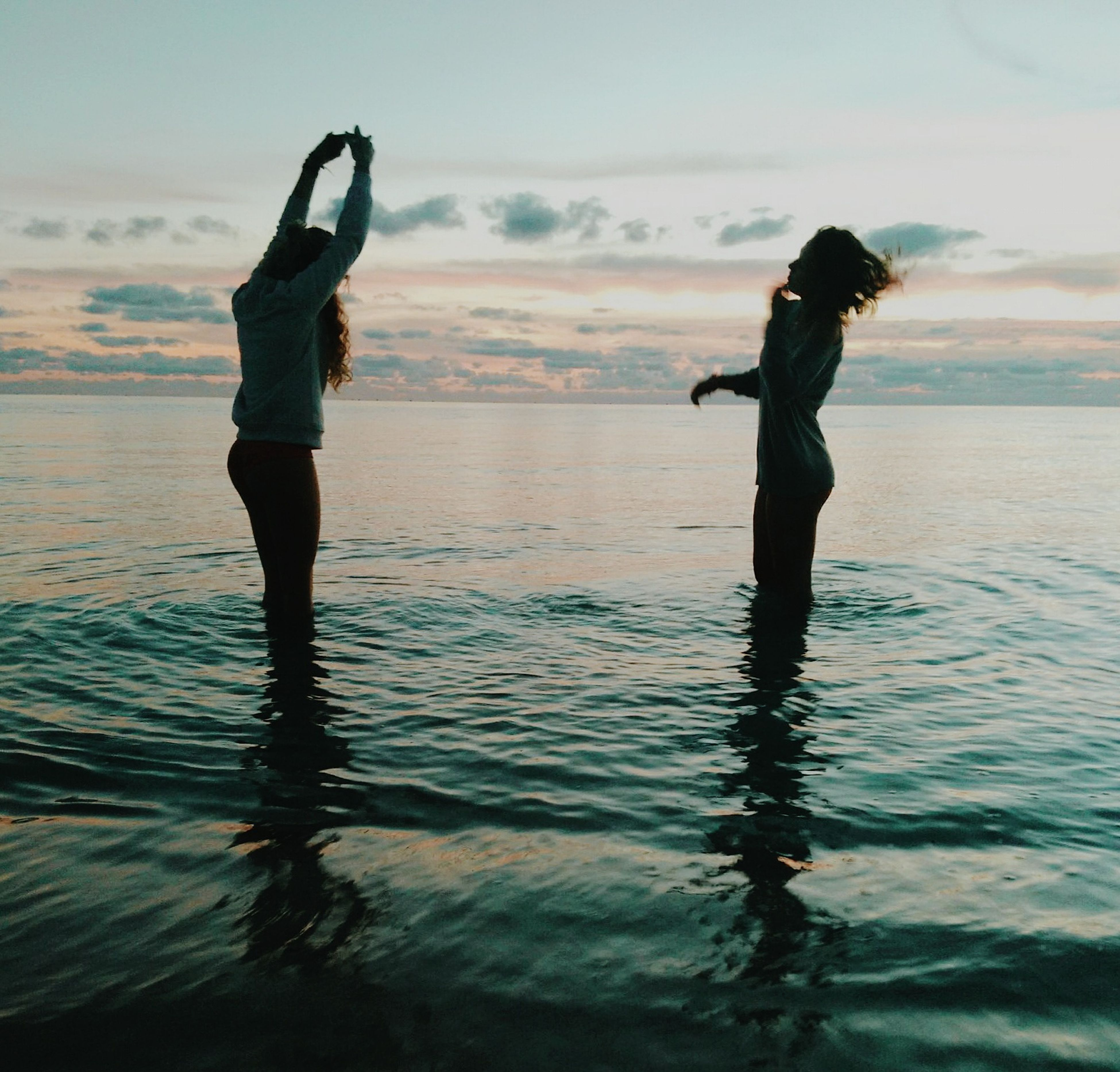 water, sea, sunset, lifestyles, leisure activity, silhouette, sky, standing, beach, reflection, full length, horizon over water, waterfront, beauty in nature, tranquil scene, scenics, vacations, tranquility