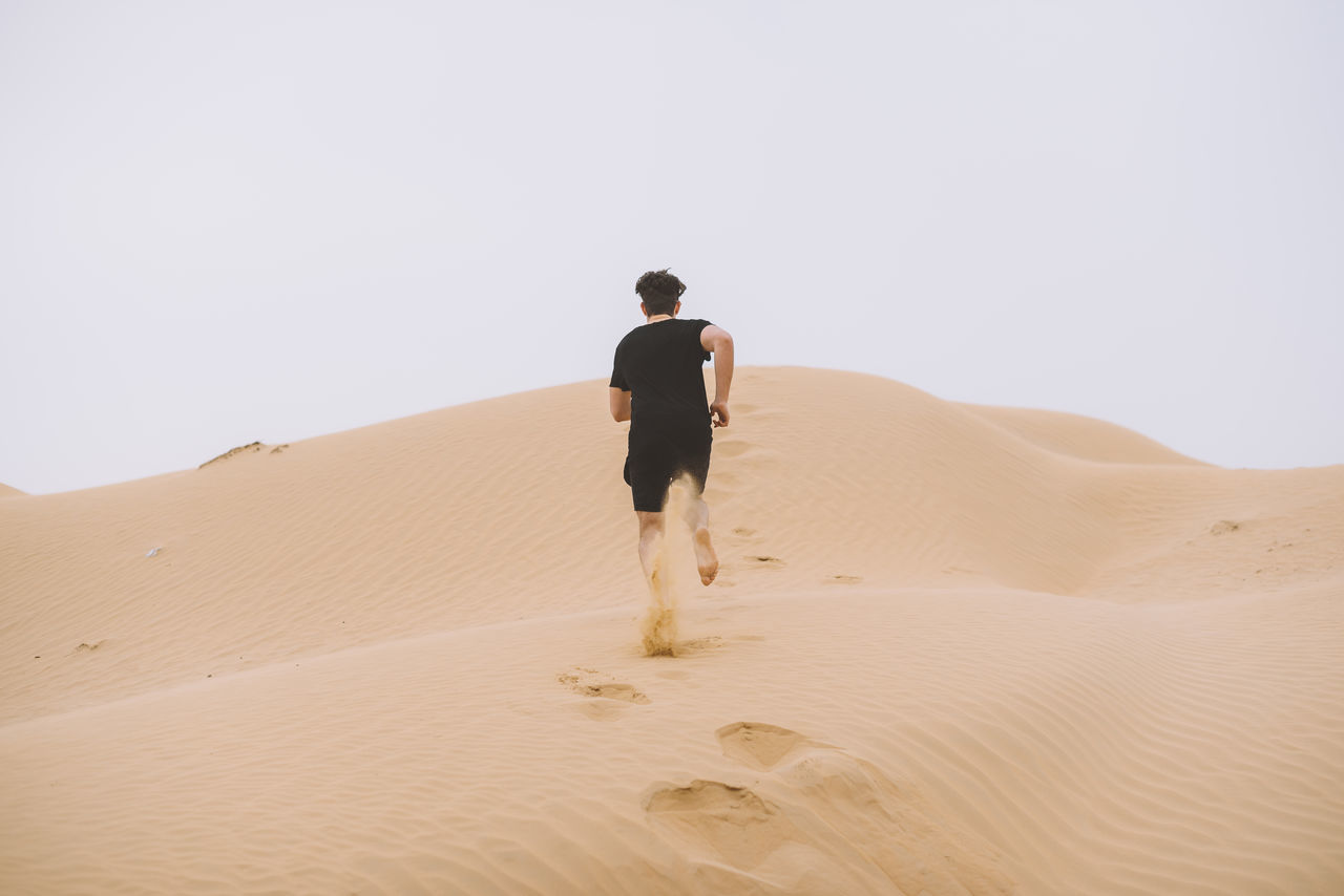 Adult Adults Only Adventure Arid Climate Day Desert Dubai Environment Extreme Terrain Full Length Heat - Temperature Landscape Men Nature One Man Only One Person Only Men Outdoors People Rear View Sand Sand Dune UAE United Arab Emirates Young Adult