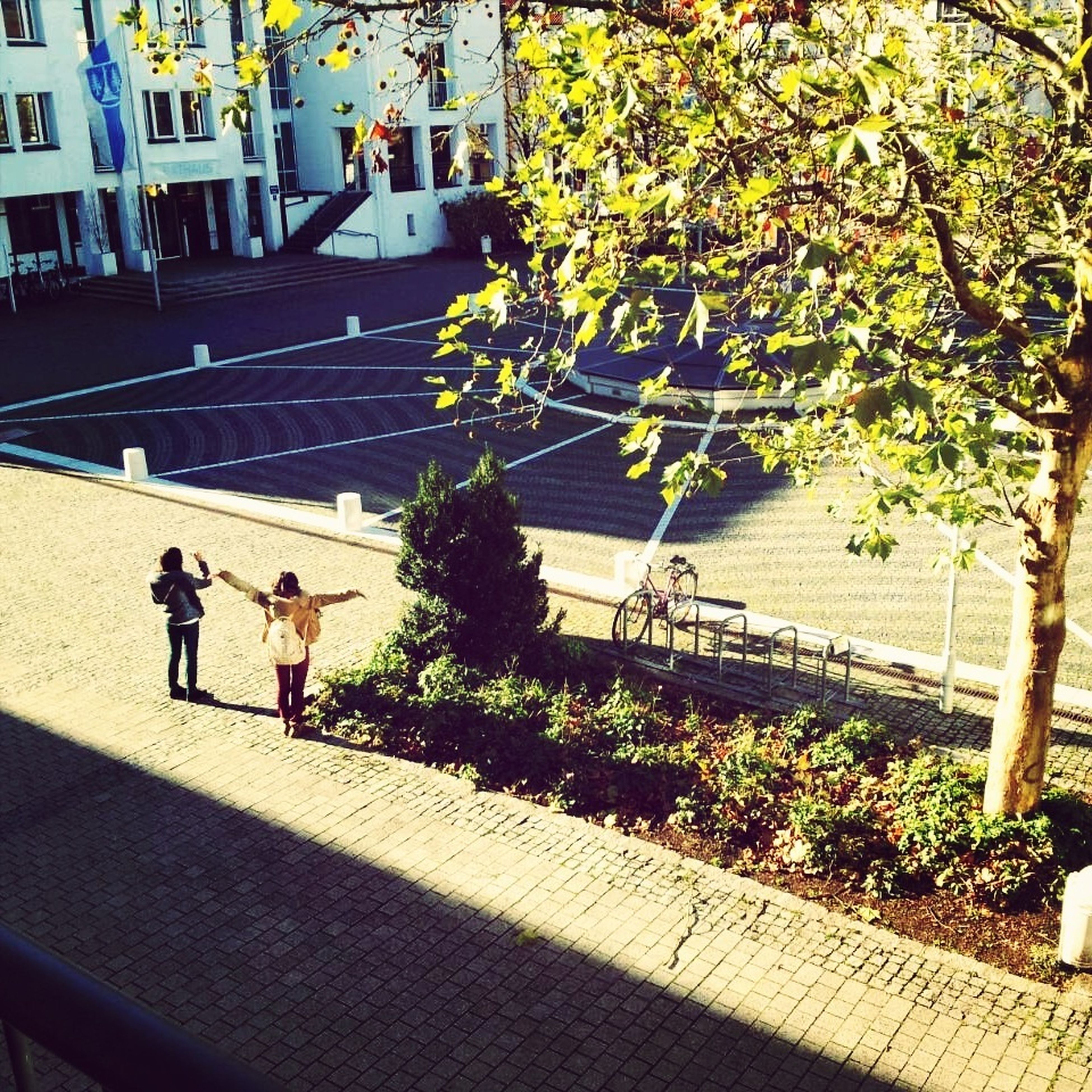 men, person, lifestyles, architecture, building exterior, walking, built structure, shadow, leisure activity, sunlight, tree, high angle view, city, city life, railing, medium group of people, day, outdoors, street