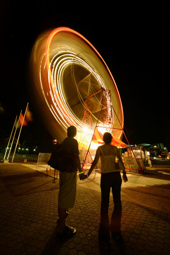 Adult Adults Only Amusementpark Arts Culture And Entertainment Blurred Motion City Couple Ferrys Wheel Holding Hands Illuminated Light Trail Long Exposure Motion Night Outdoors People Sky Speed Theme Park