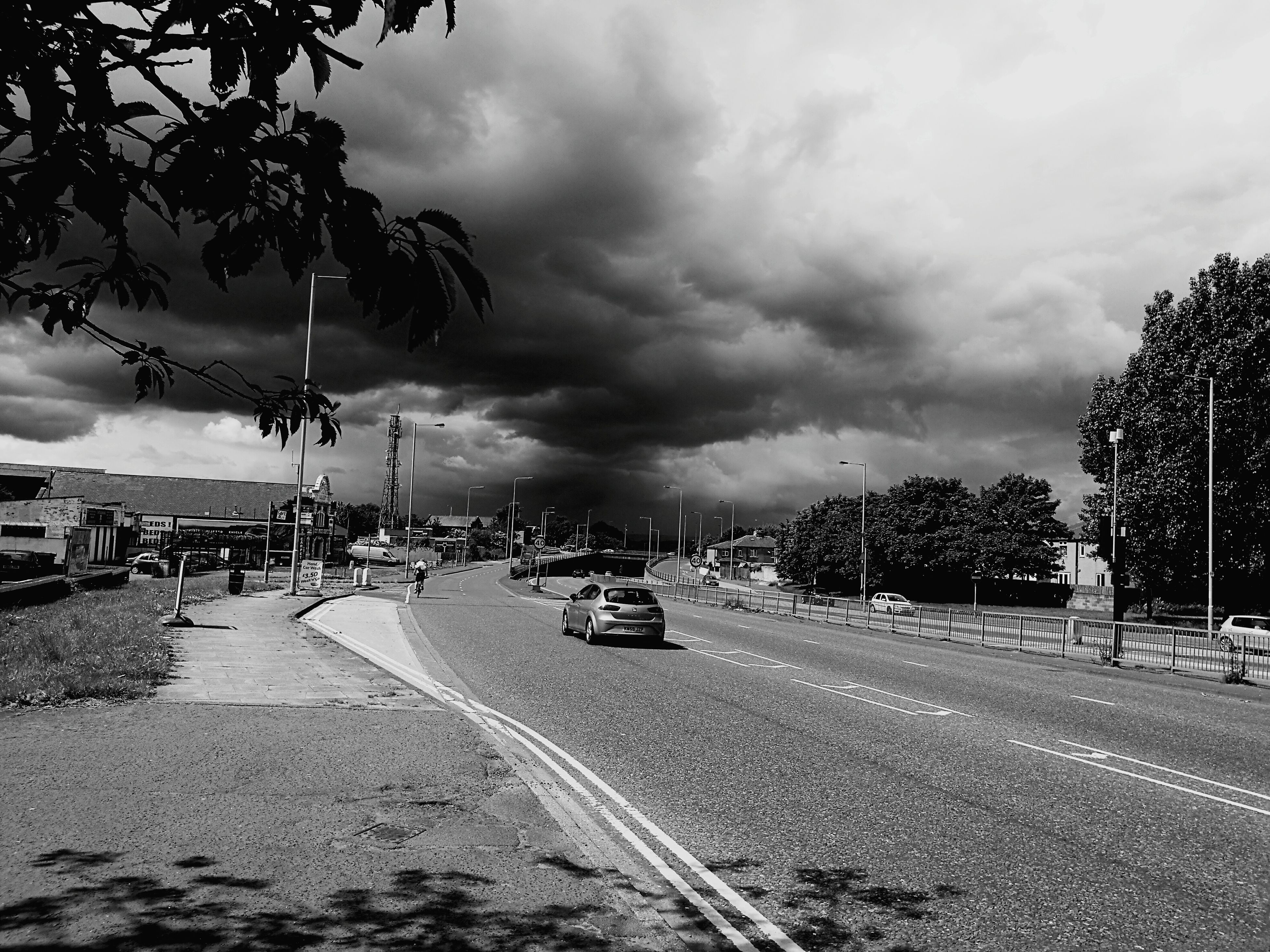 sky, transportation, cloud - sky, road, tree, the way forward, cloudy, street, land vehicle, car, mode of transport, cloud, street light, road marking, diminishing perspective, vanishing point, outdoors, overcast, incidental people, weather