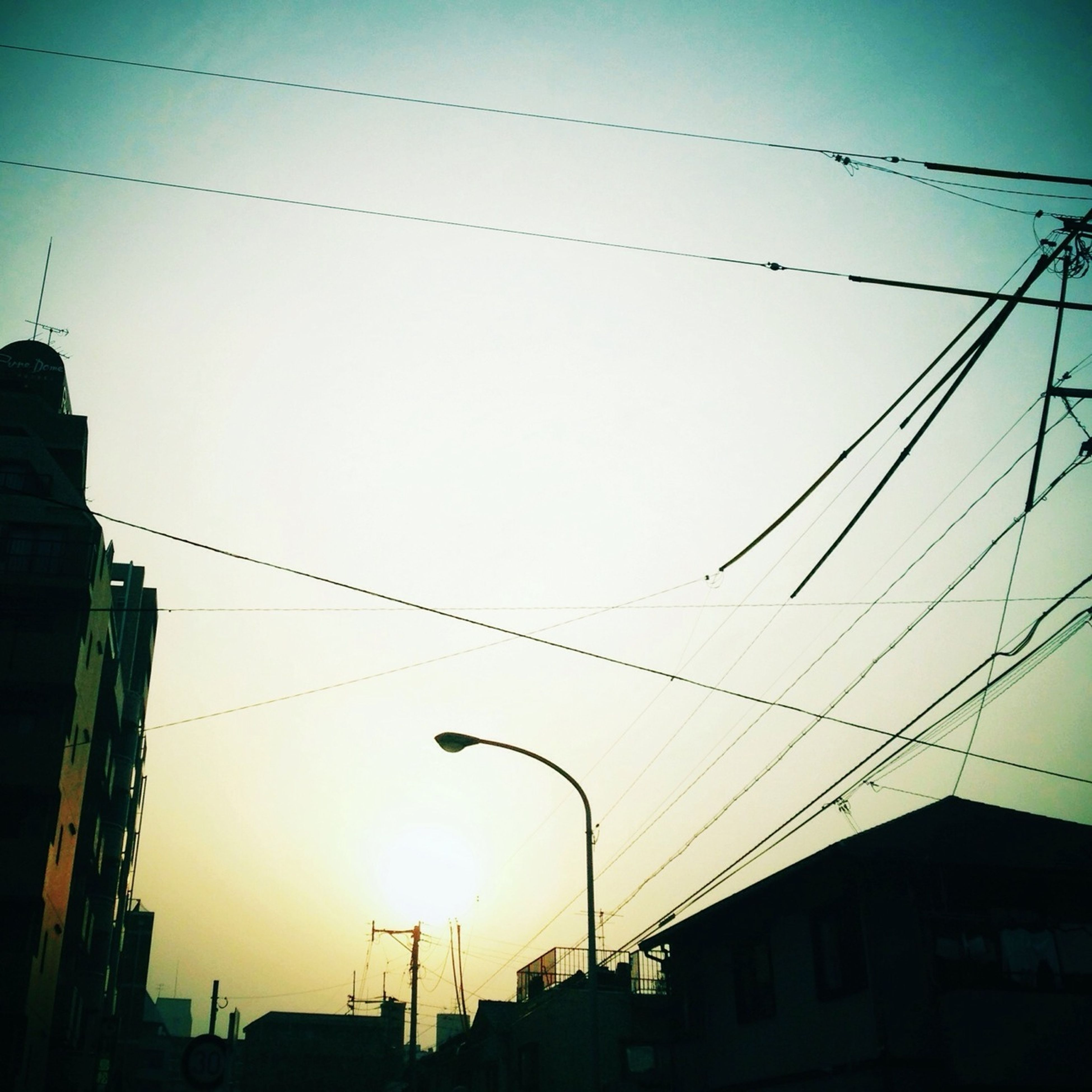 power line, architecture, building exterior, built structure, cable, sunset, low angle view, electricity pylon, electricity, silhouette, power supply, connection, sky, power cable, residential structure, house, building, residential building, dusk, city