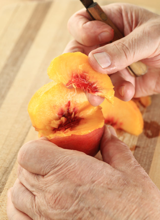 Cutting slices from a fresh peach on cutting board Copy Space Cutting Board Fingers Food Preparation Fresh Fruit Hands Healthy Eating Holding Juicy Man Natural Light Natural Lighting One Person Overhead Paring Knife Peach POV Raw Food Ripe Senior Tasty Textures Vertical Wet