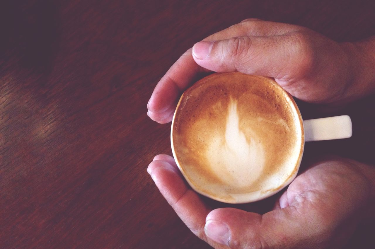 human hand, coffee - drink, coffee cup, drink, refreshment, food and drink, holding, frothy drink, cappuccino, table, human body part, real people, one person, saucer, froth art, freshness, high angle view, indoors, latte, close-up, healthy eating, lifestyles, day, people