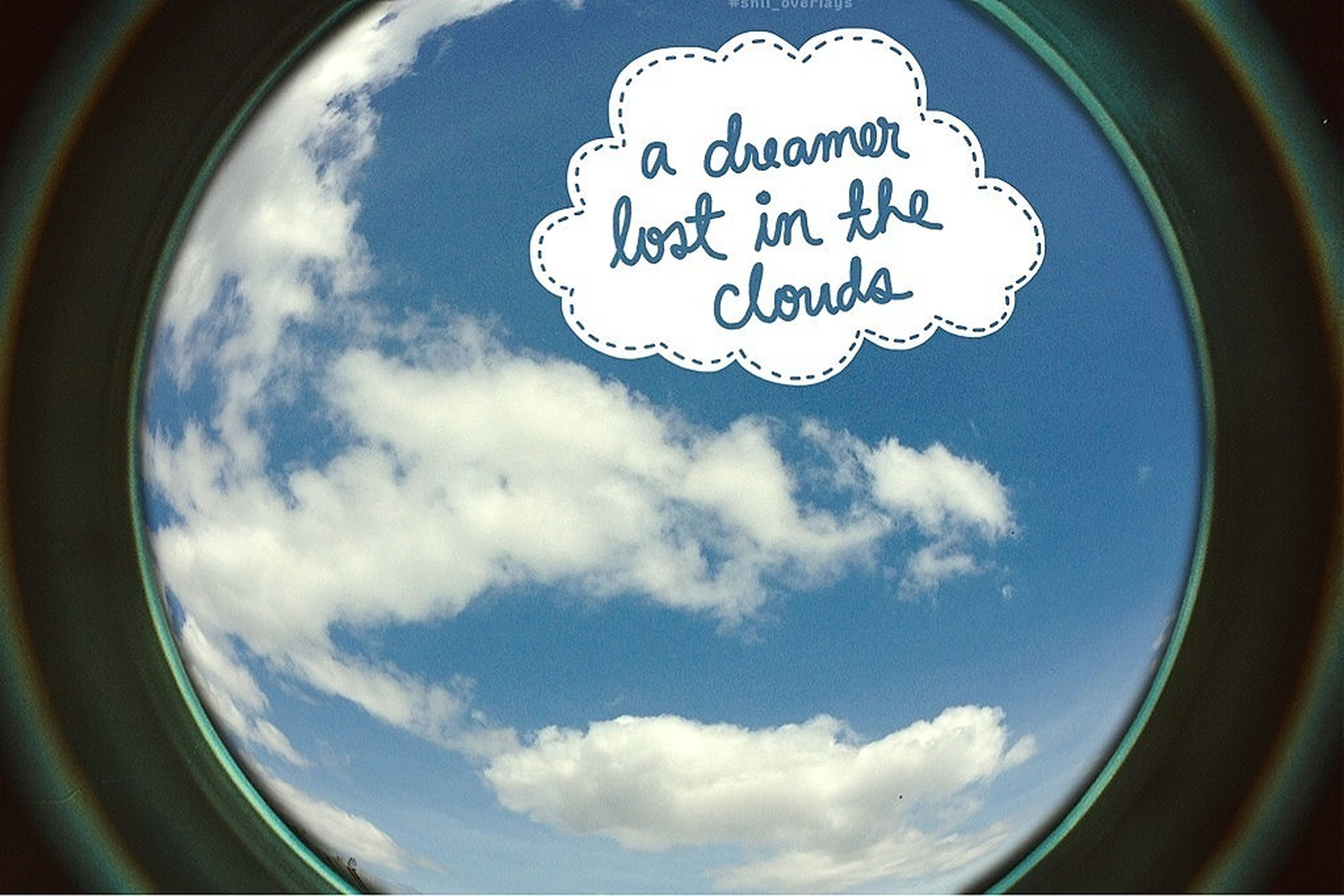 text, sky, communication, cloud - sky, circle, western script, transportation, glass - material, transparent, geometric shape, window, capital letter, low angle view, cloud, close-up, no people, cloudy, day, reflection, fish-eye lens