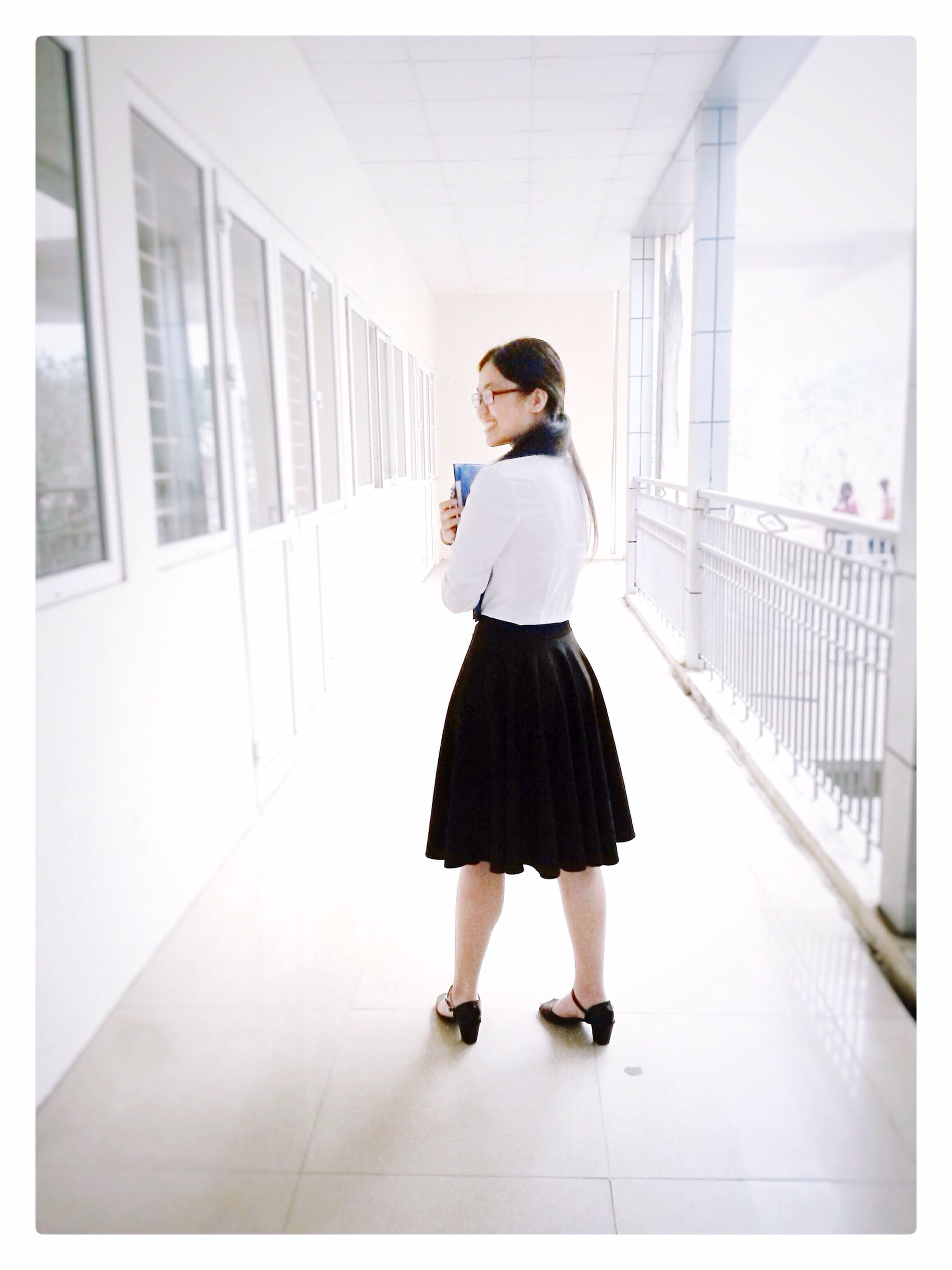 young adult, full length, lifestyles, casual clothing, indoors, architecture, built structure, young women, standing, person, front view, looking at camera, leisure activity, portrait, walking, corridor, building exterior, building