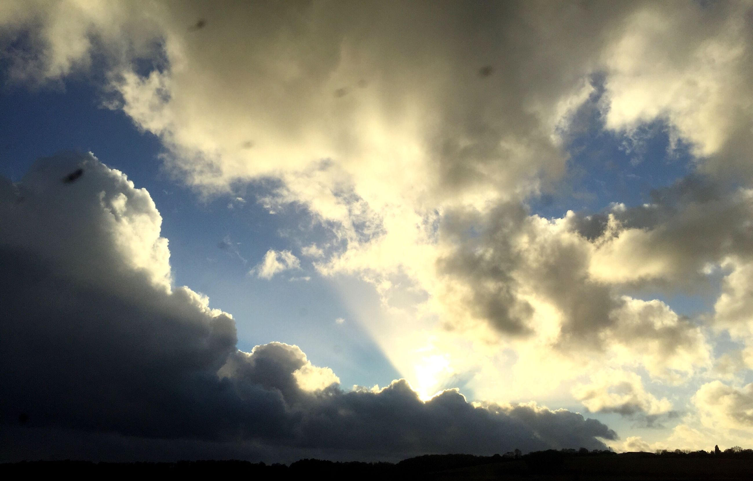 sky, cloud - sky, beauty in nature, scenics, low angle view, cloudy, tranquil scene, sun, tranquility, cloud, nature, silhouette, sunbeam, sunlight, cloudscape, idyllic, sunset, outdoors, no people, majestic