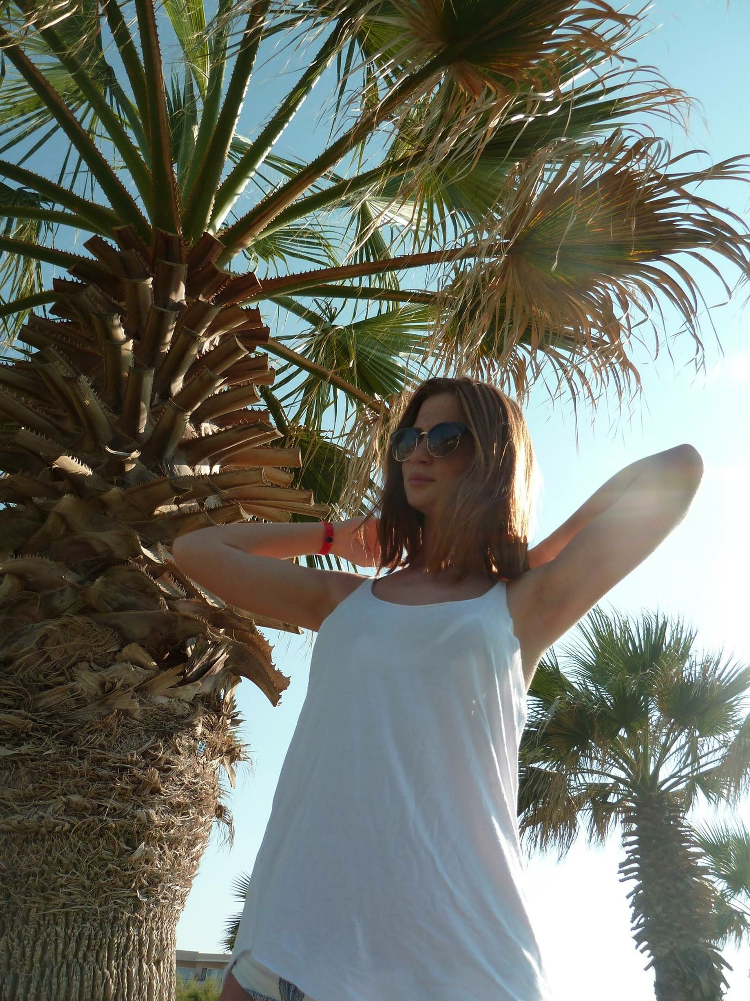 tree, lifestyles, leisure activity, palm tree, young adult, young women, person, low angle view, casual clothing, clear sky, looking at camera, front view, portrait, standing, smiling, sky, long hair, outdoors