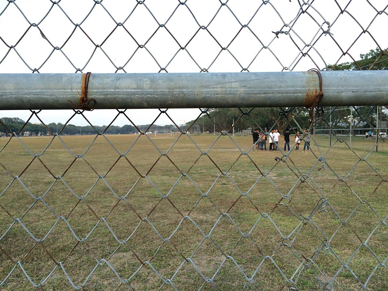 chainlink fence, safety, real people, protection, security, metal, day, togetherness, playing field, teamwork, sport, standing, outdoors, team sport, sports team, competitive sport, grass, group of people, playing, men, competition, sky, nature, adults only, people, adult