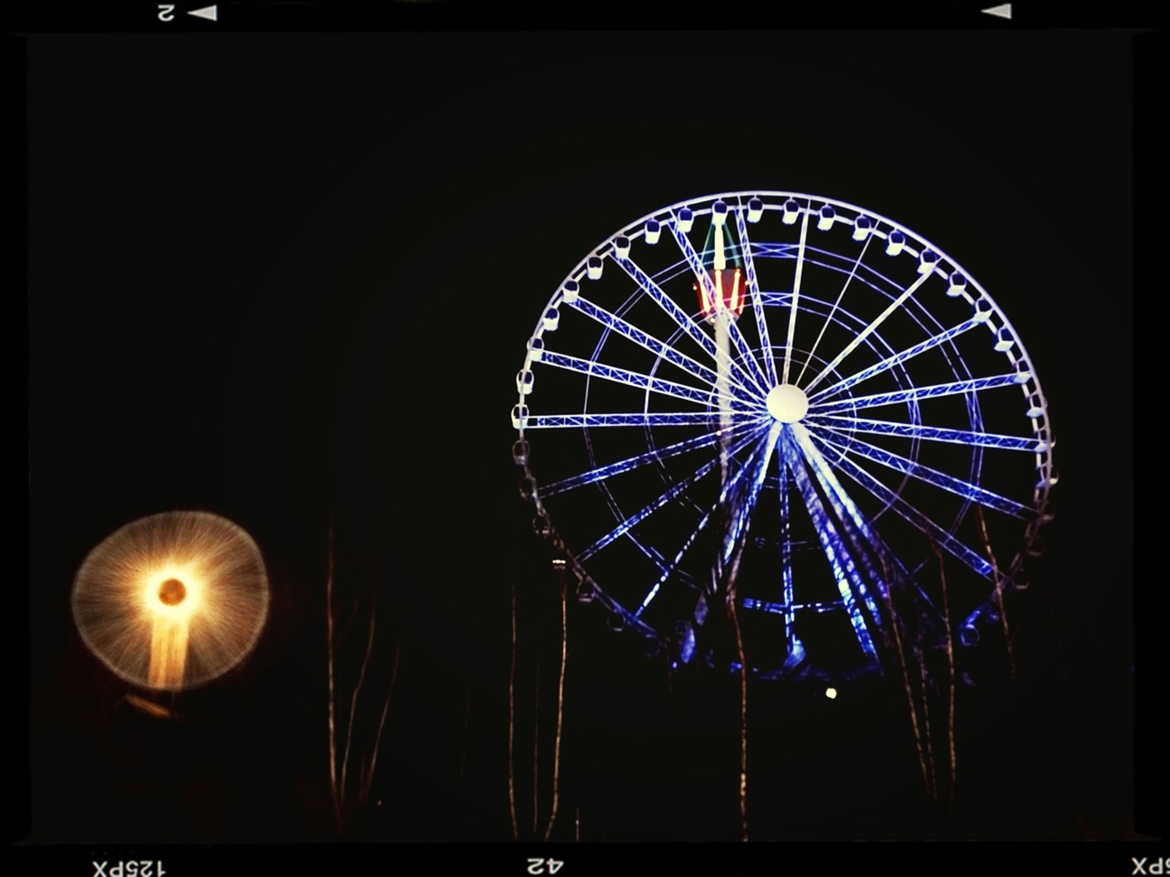 low angle view, illuminated, night, circle, arts culture and entertainment, ferris wheel, amusement park ride, amusement park, glowing, lighting equipment, sky, transfer print, no people, built structure, geometric shape, decoration, outdoors, auto post production filter, clear sky, architecture
