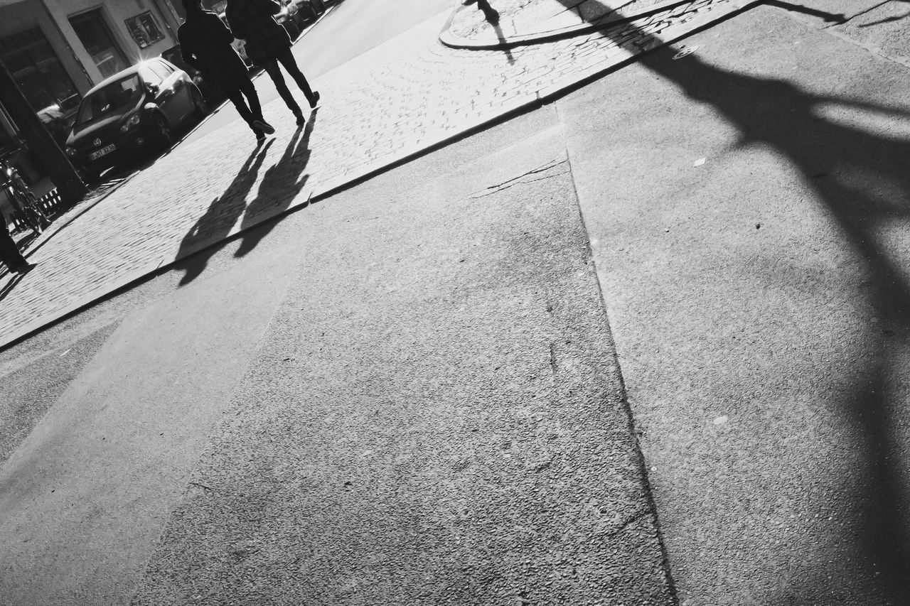 sunlight, shadow, street, real people, outdoors, day, low section, sidewalk, road, city, one person, people