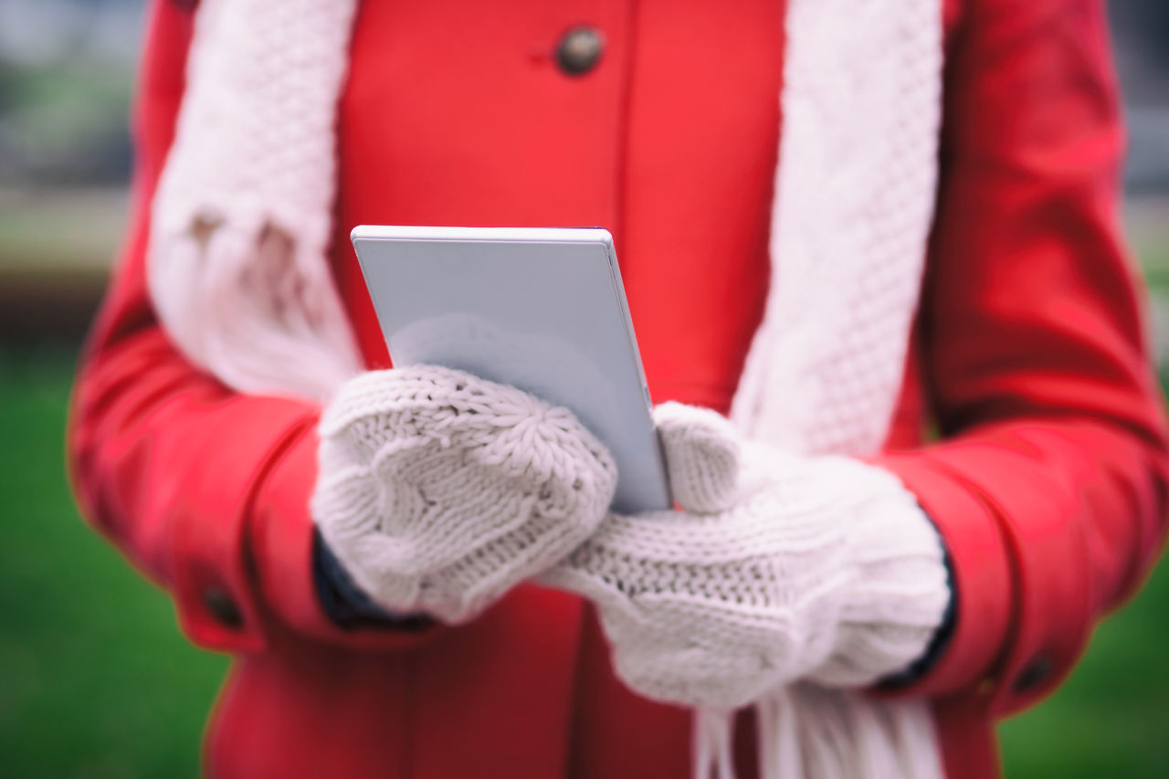 red, human hand, technology, midsection, real people, human body part, wireless technology, holding, warm clothing, one person, women, outdoors, close-up, day, winter, young women, young adult, people