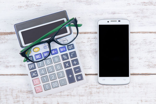 Top view of calculator, glasses and smartphone on the accountant white table.Business concept. Communication Connection Day Digital Tablet High Angle View Internet Mobile Phone No People Outdoors Portability Portable Information Device Smart Phone Technology Wireless Technology